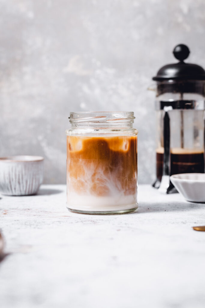 A glass filled with swirling iced coffee.