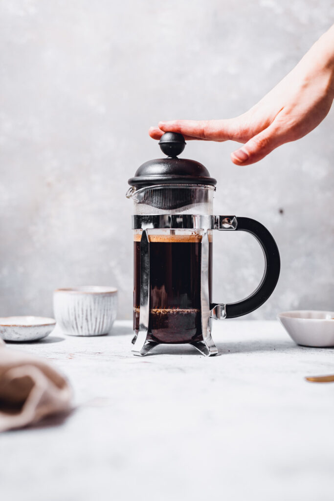 A hand pressing down on a French press filled with coffee.
