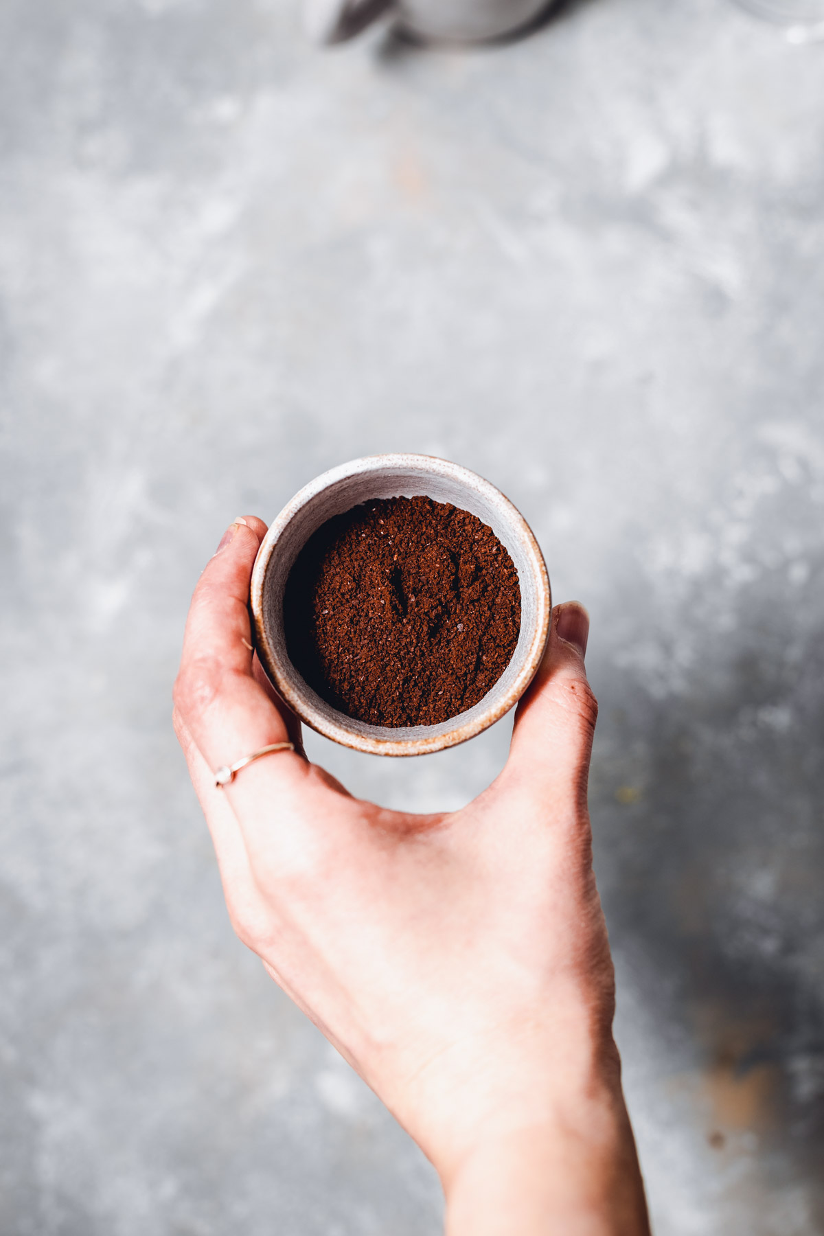 A hand holding a small bowl filled with ground coffee.