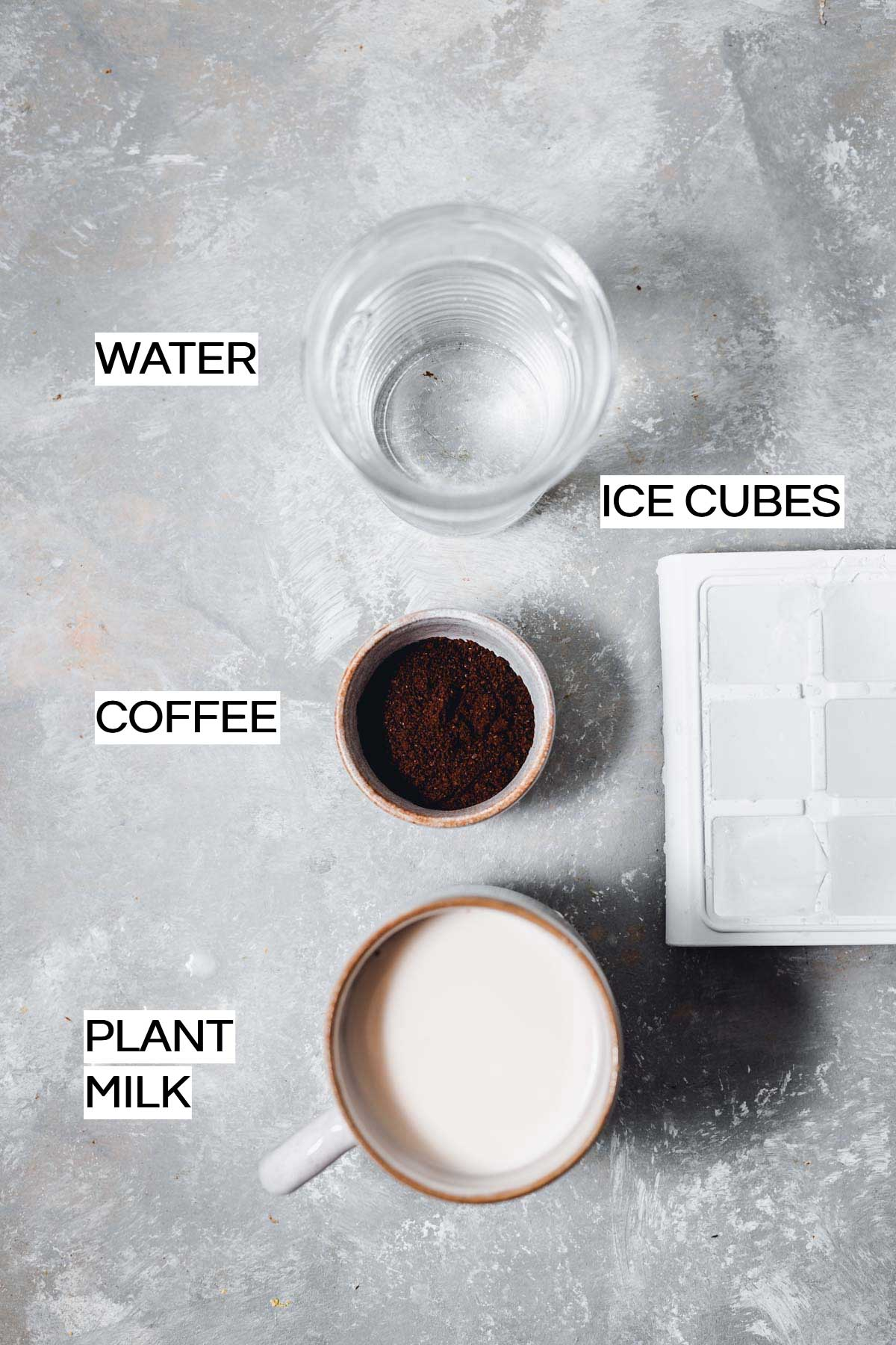 Water, coffee, plant milk and ice cubes laid out on a flat grey surface.