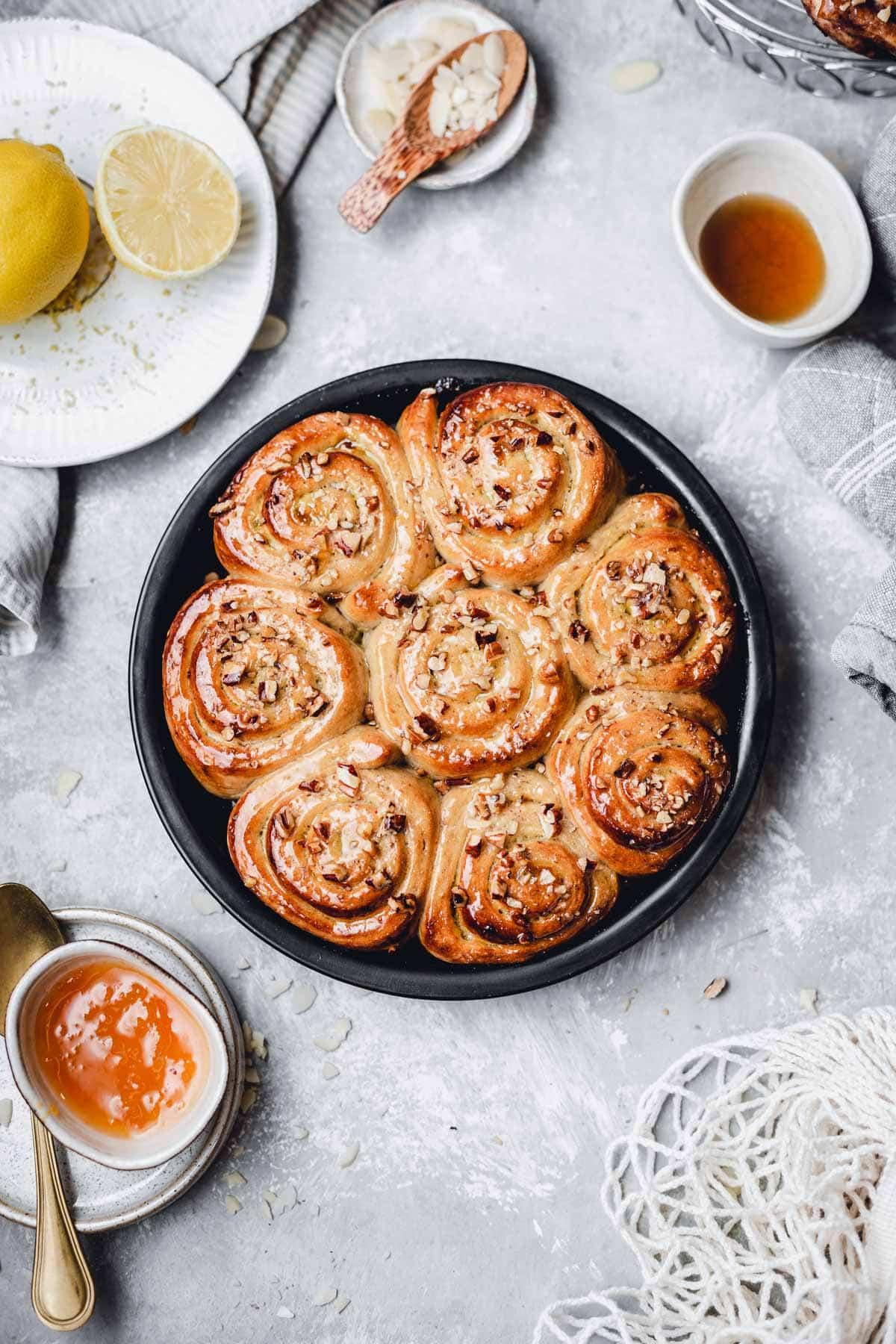 An overhead view of a round cake tin featuring vegan lemon rolls.