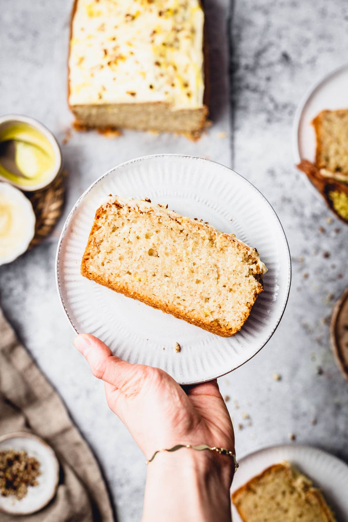 A hand holding a plate featuring a slice of lemon cake.