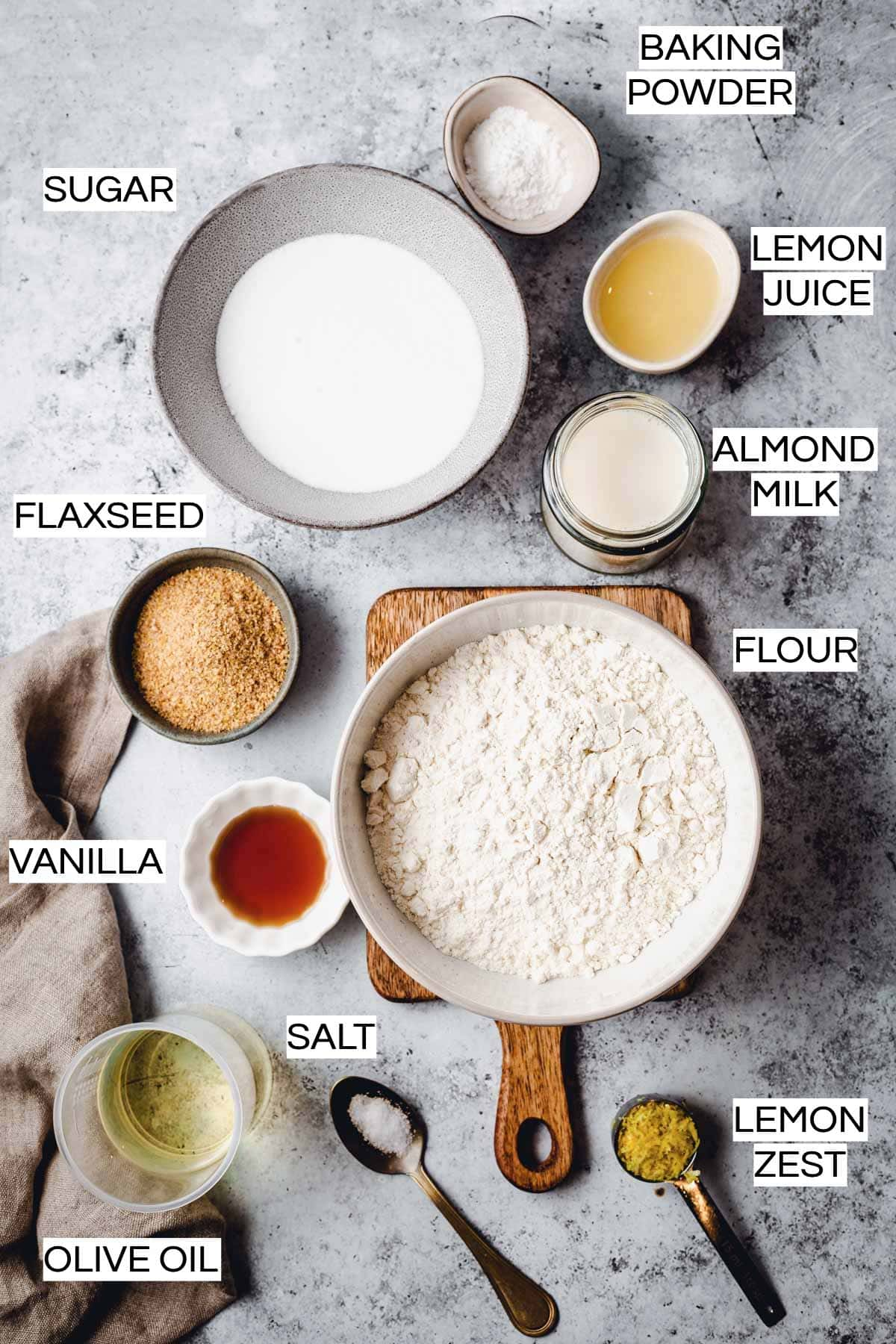 Various ingredients needed to bake a lemon cake laid out on a flat grey surface.