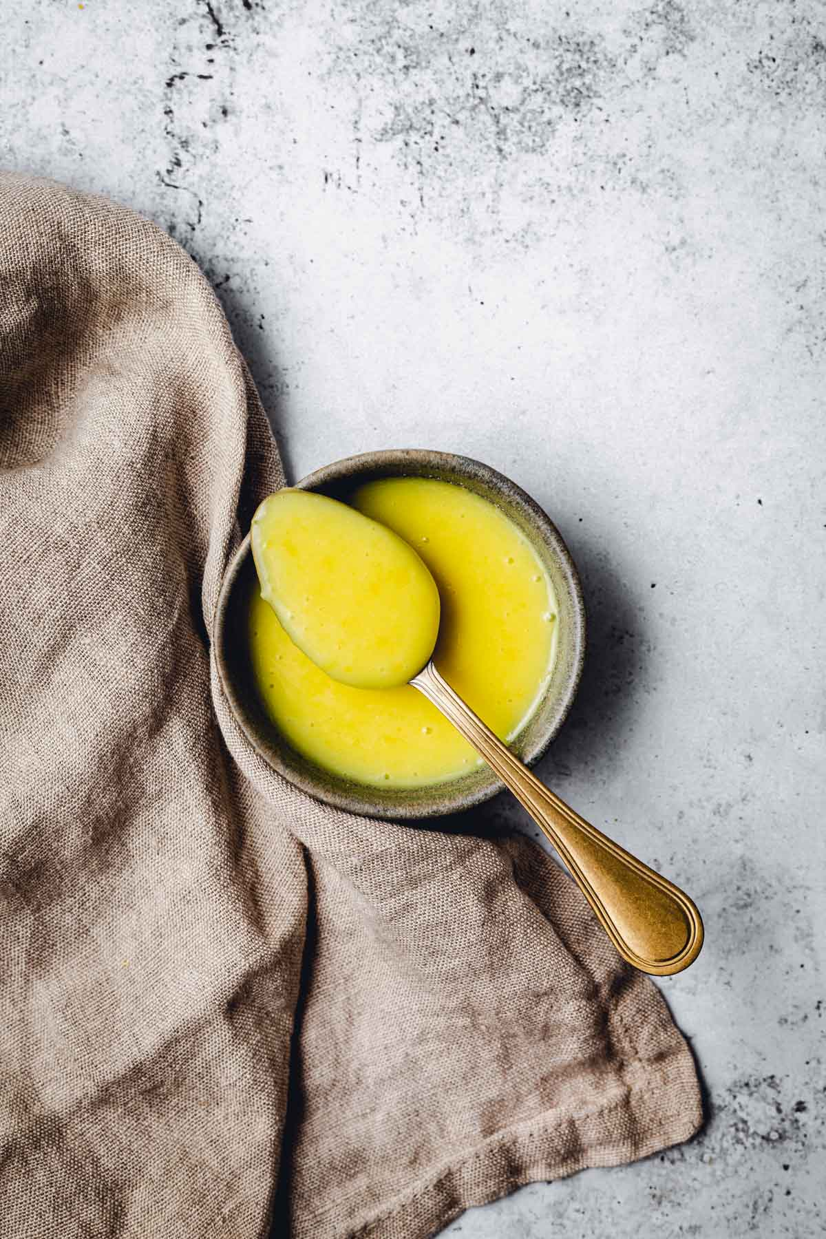 A small bowl containing lemon curd and a golden spoon with a piece of linen on the left side.