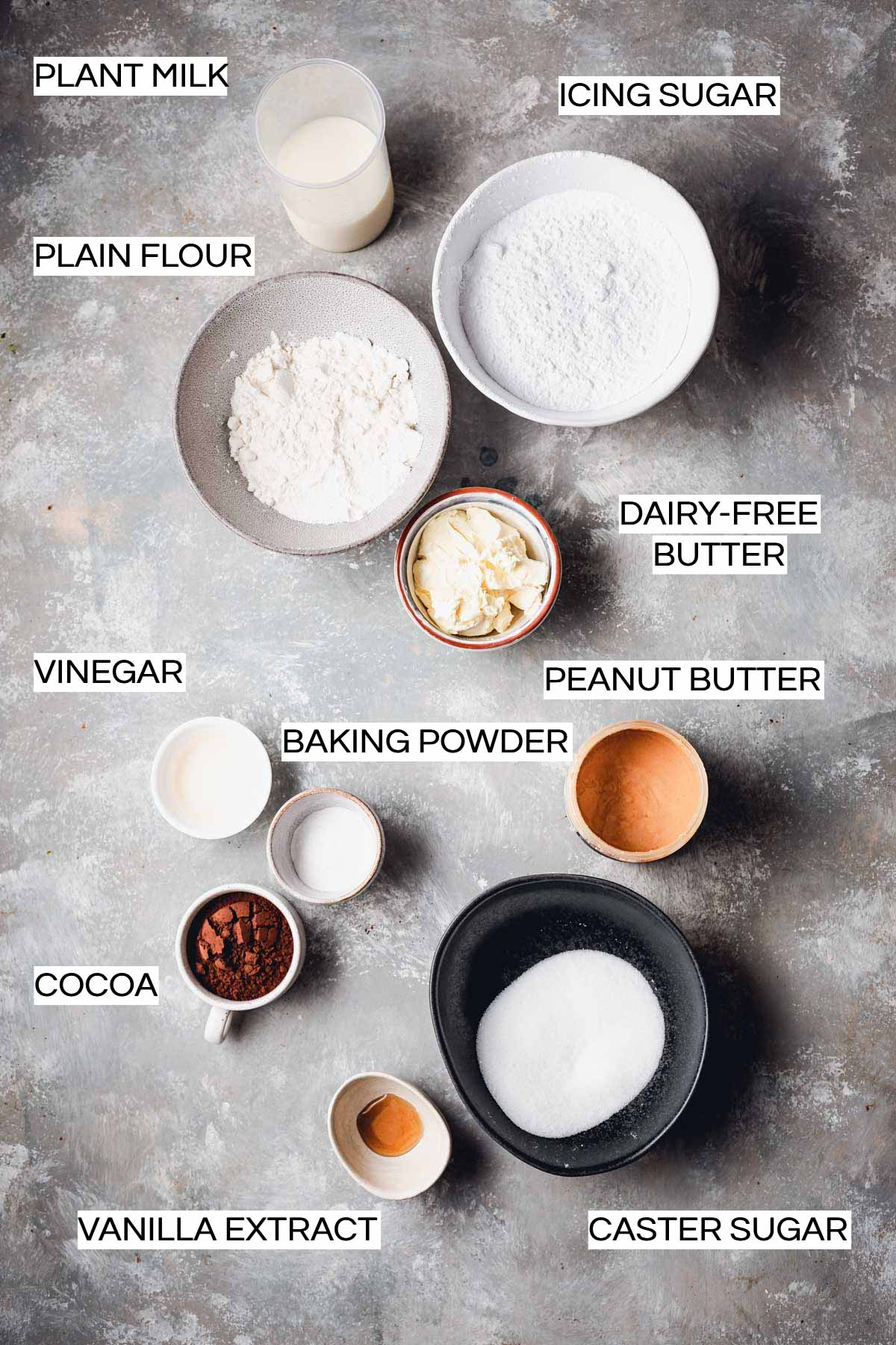 Various ingredients needed to bake cupcakes laid out in bowls on a flat surface.