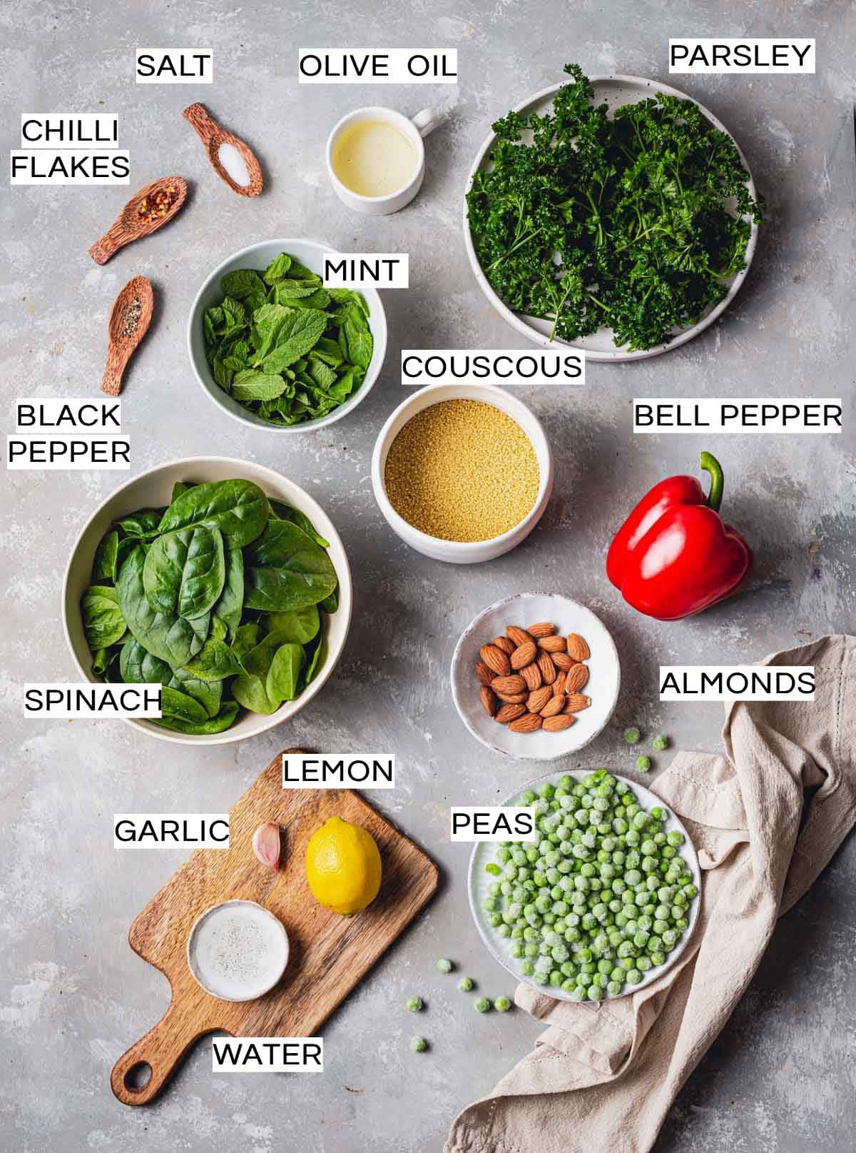 An overhead view of all ingredients needed to make couscous salad laid out in plates and bowls.