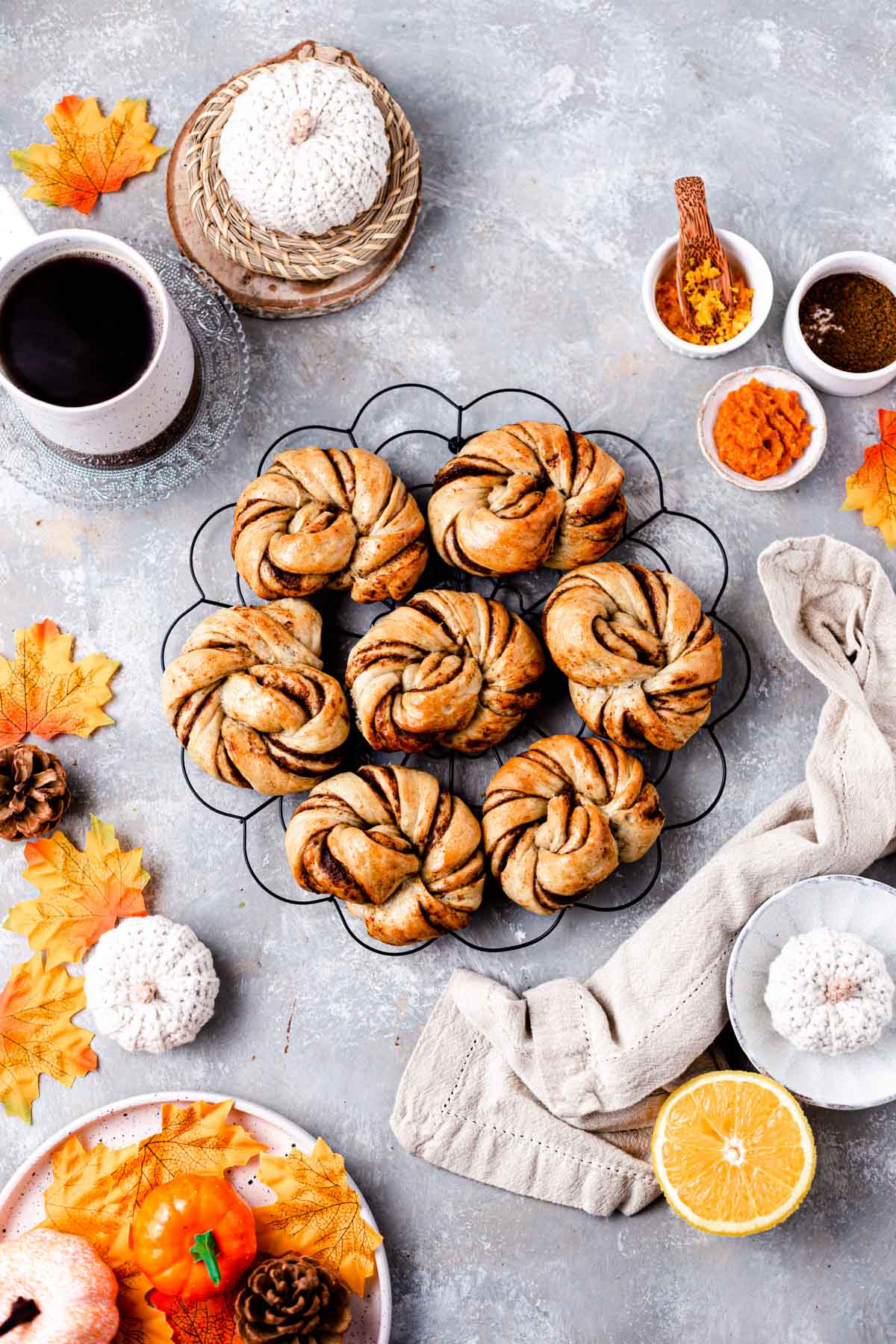 Seven pumpkin rolls placed on a round cooling rack and surrounded by orange leaves, coffee cup, pumpkin puree and more.