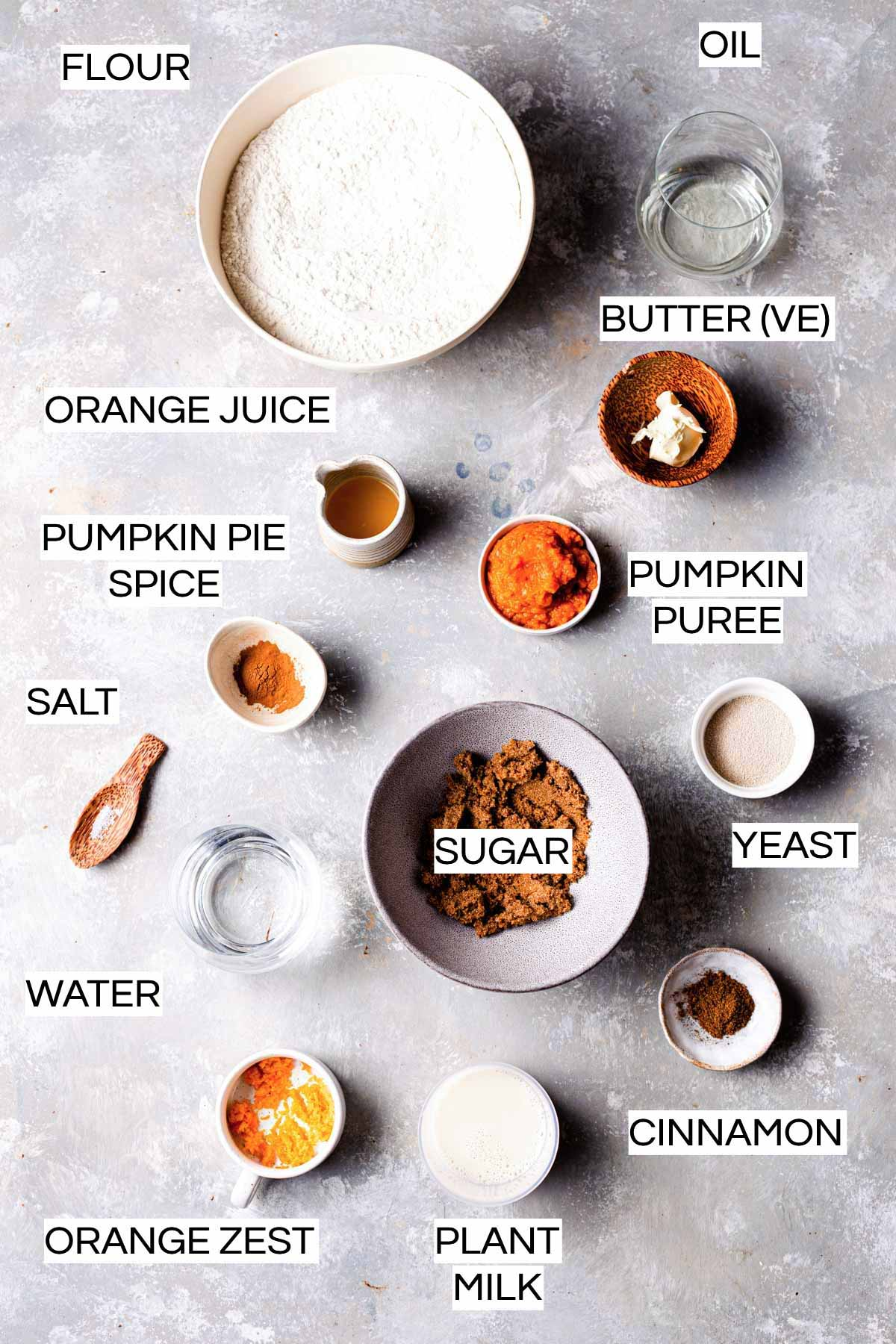 All ingredients needed to bake vegan pumpkin rolls laid out on a grey surface.