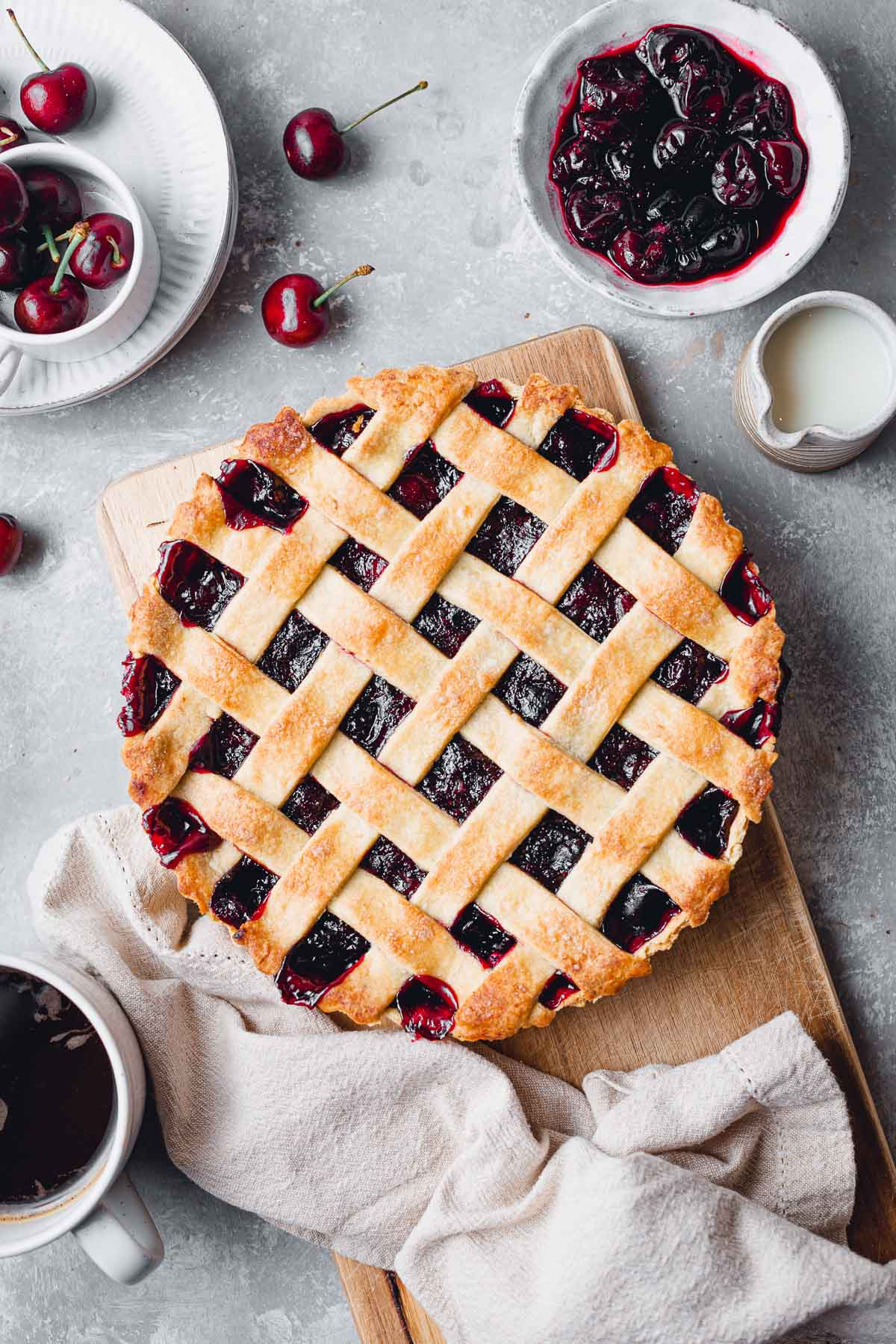 A baked vegan cherry pie placed on a wooden board surrounded by cherries and coffee.