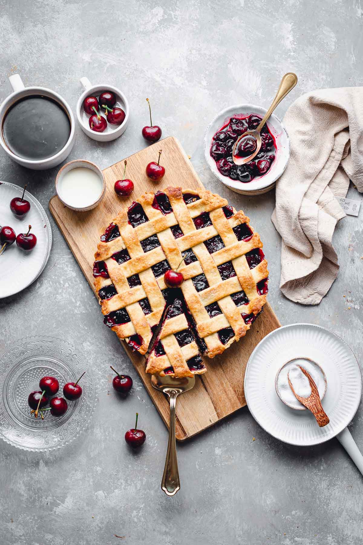 An overhead view of cherry pie with one slice being taken out and various ingredients scattered around.