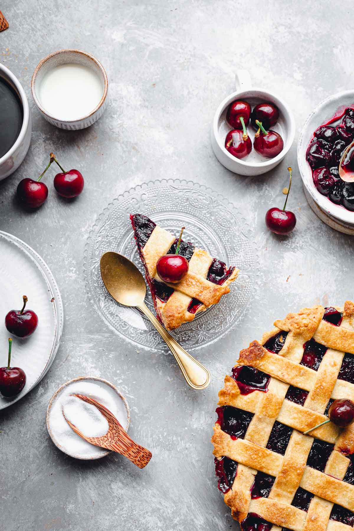 A slice of cherry pie placed on a round glass plate with various ingredients scattered around.