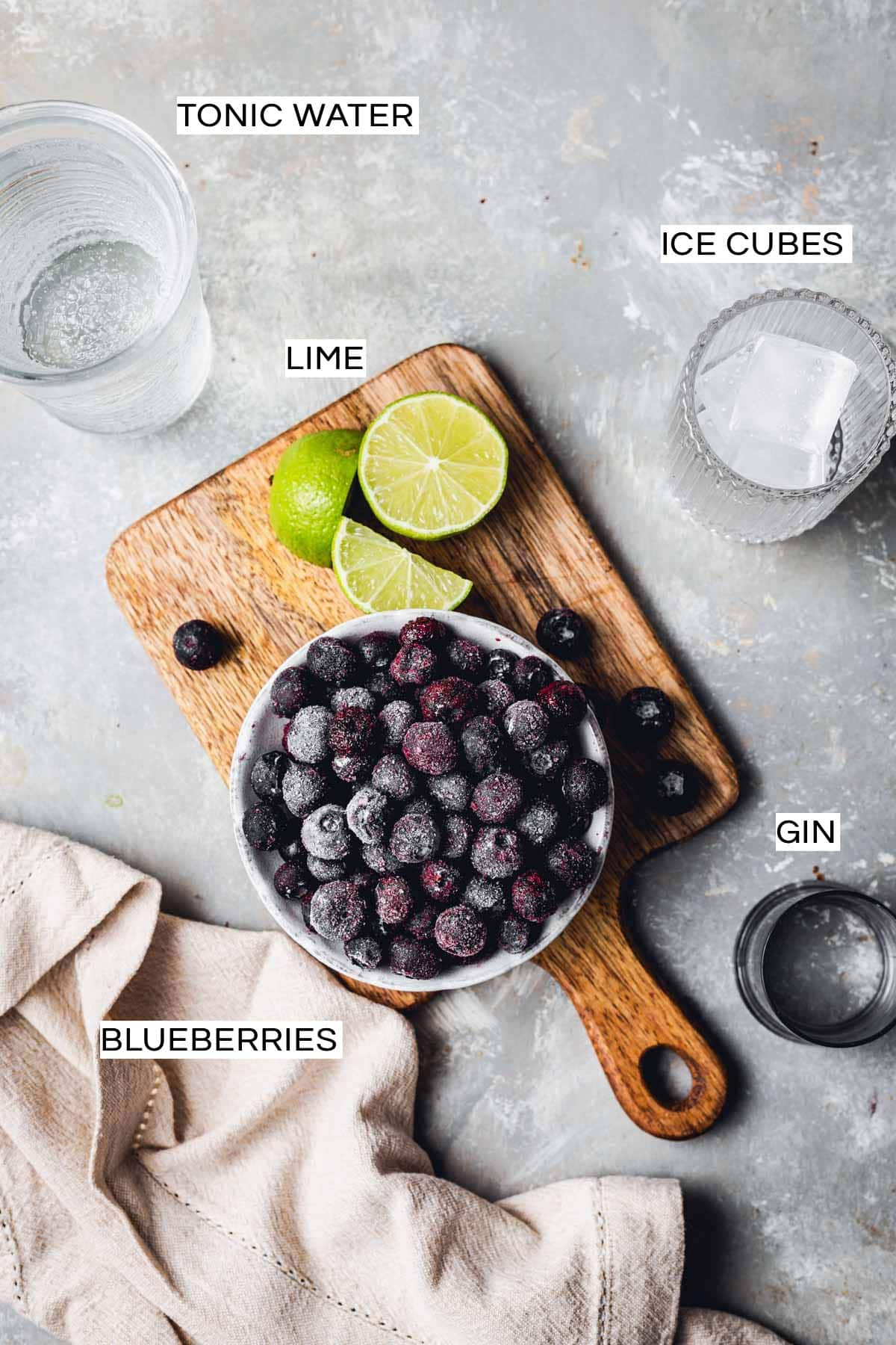All ingredients needed to make a gin cocktail placed on a grey surface.