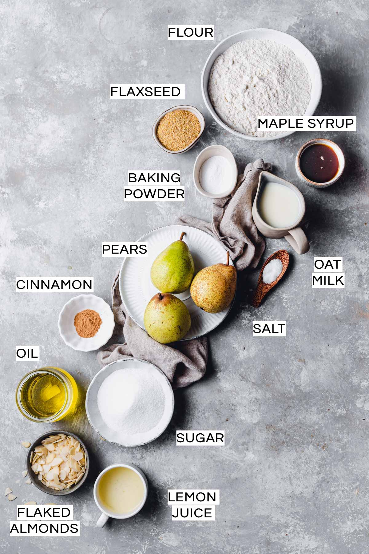 Various ingredients needed to make a vegan pear cake laid out on a grey surface.