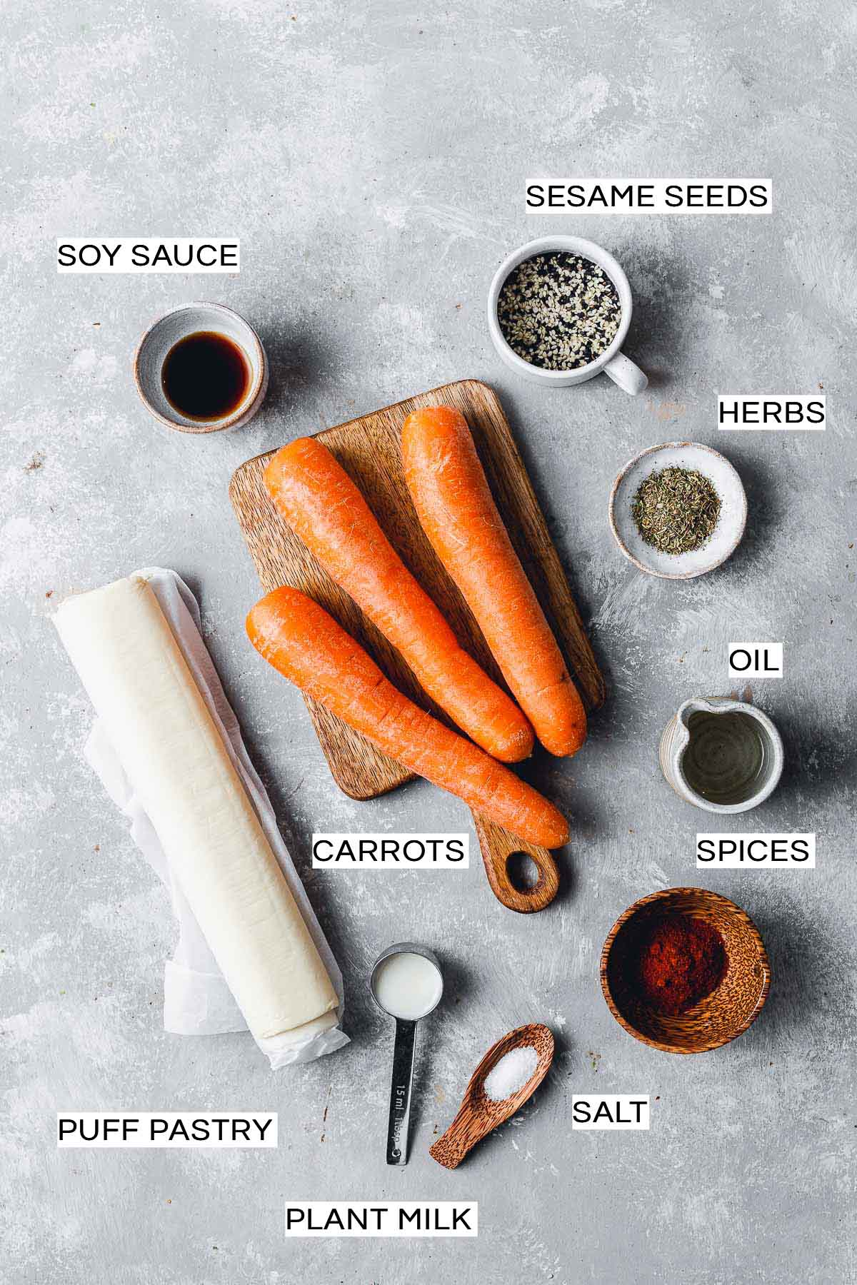 All ingredients needed to make carrots in a blanket on a flat surface.