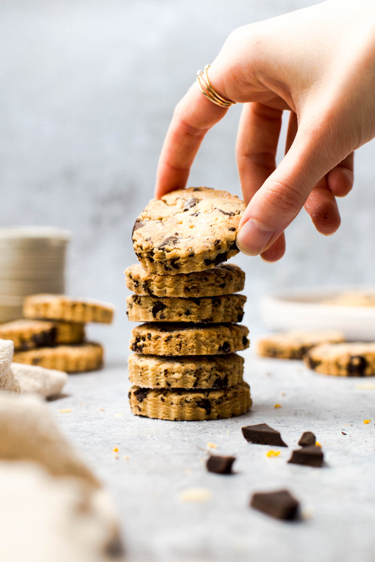 A hand reaching out for a stack of shortbread biscuits.