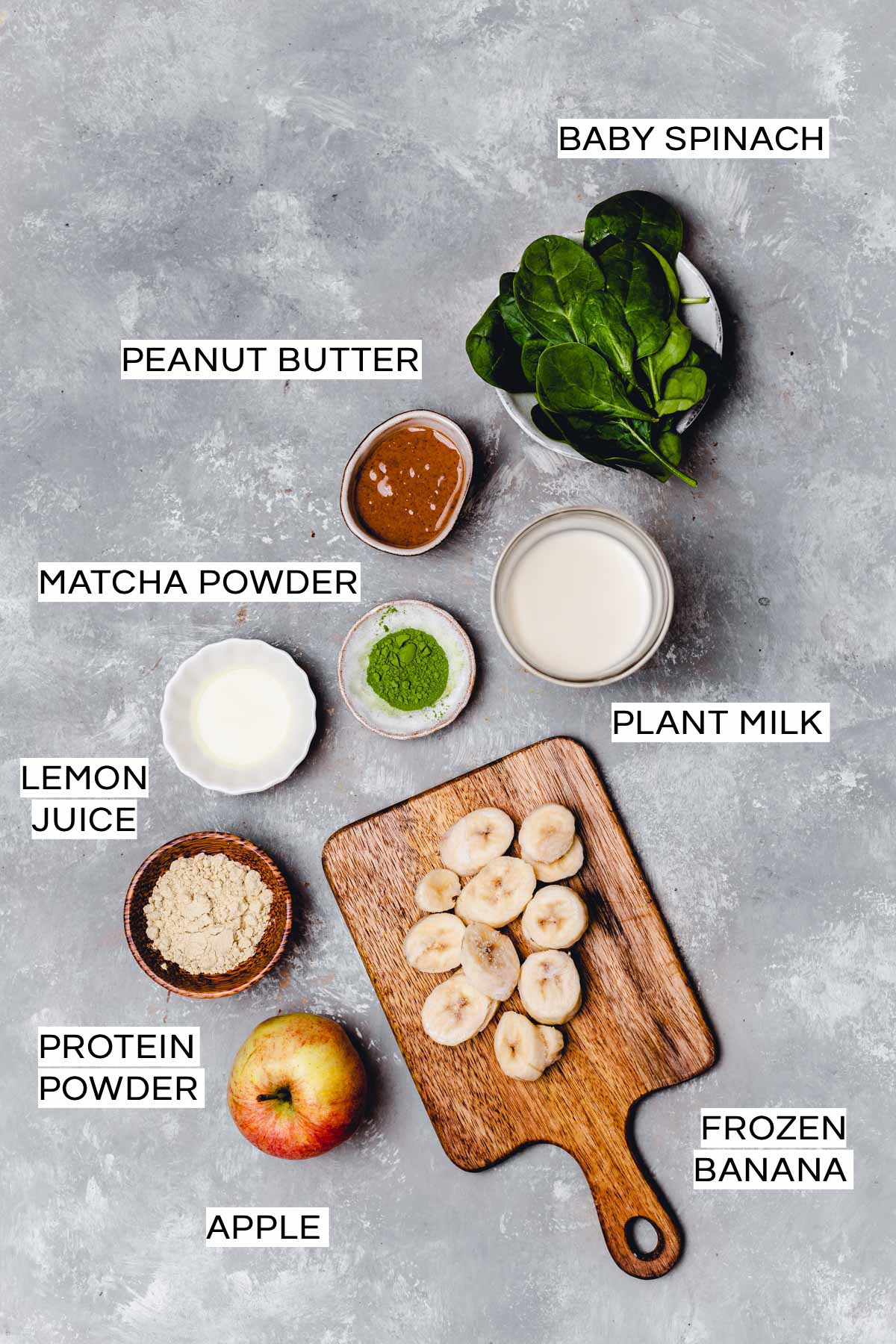 All ingredients needed to make a matcha protein shake laid out on a grey surface.