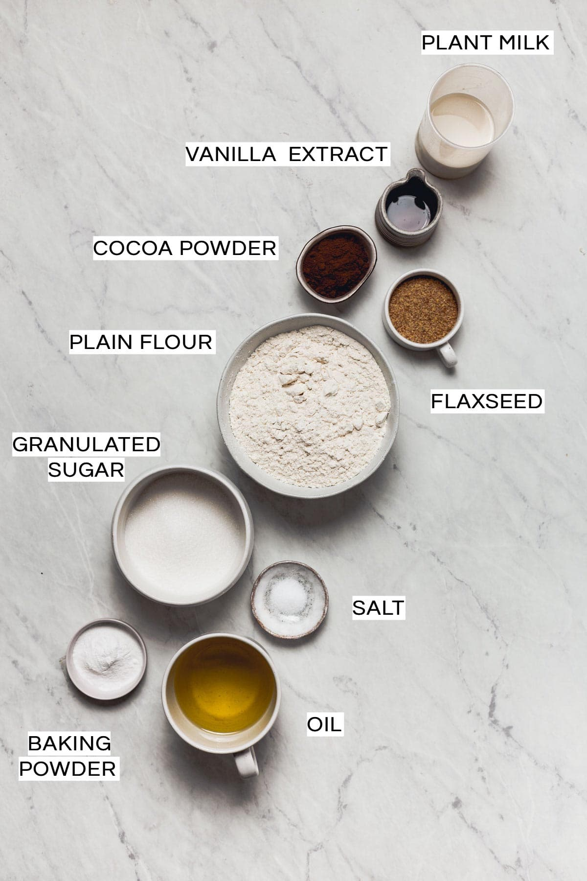 All the ingredients needed to make a coffee cake placed in bowls on a marble background.