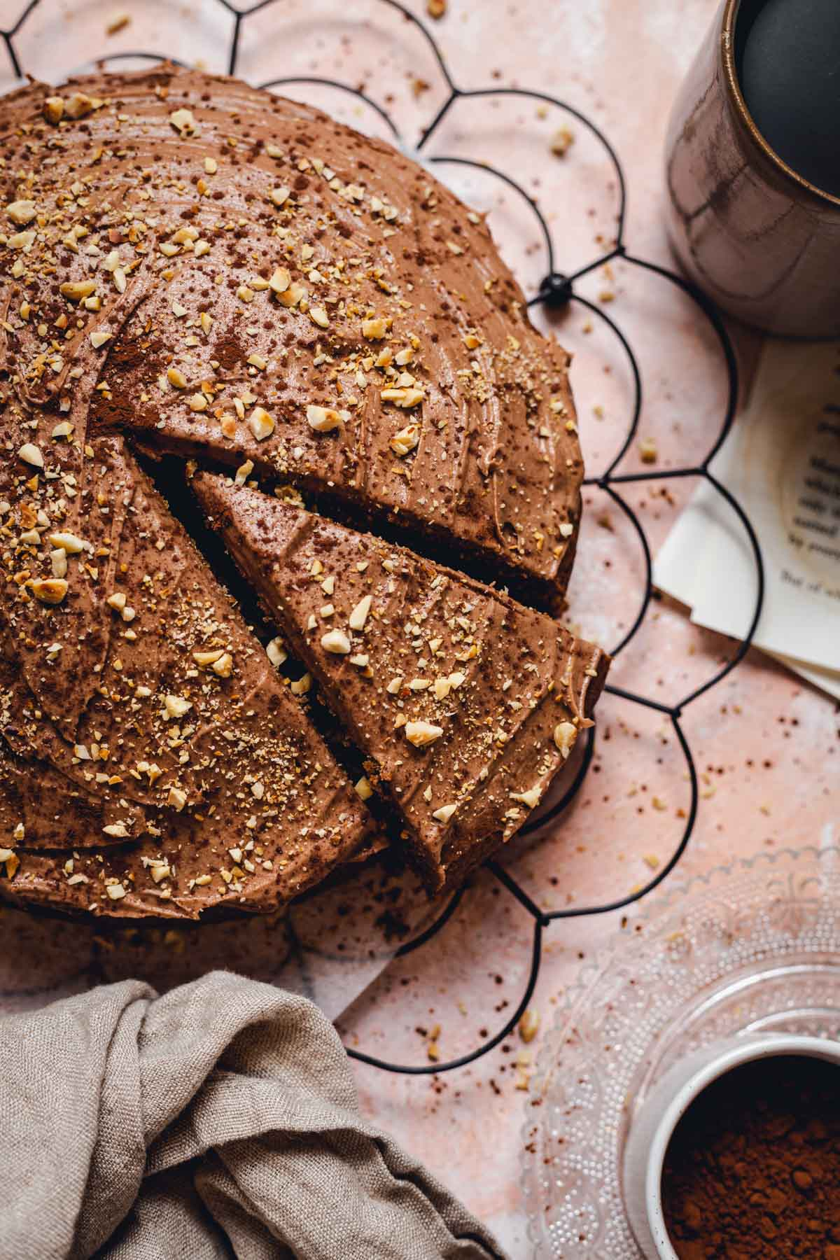 A round coffee cake placed on a black cooling rack with various objects around it.