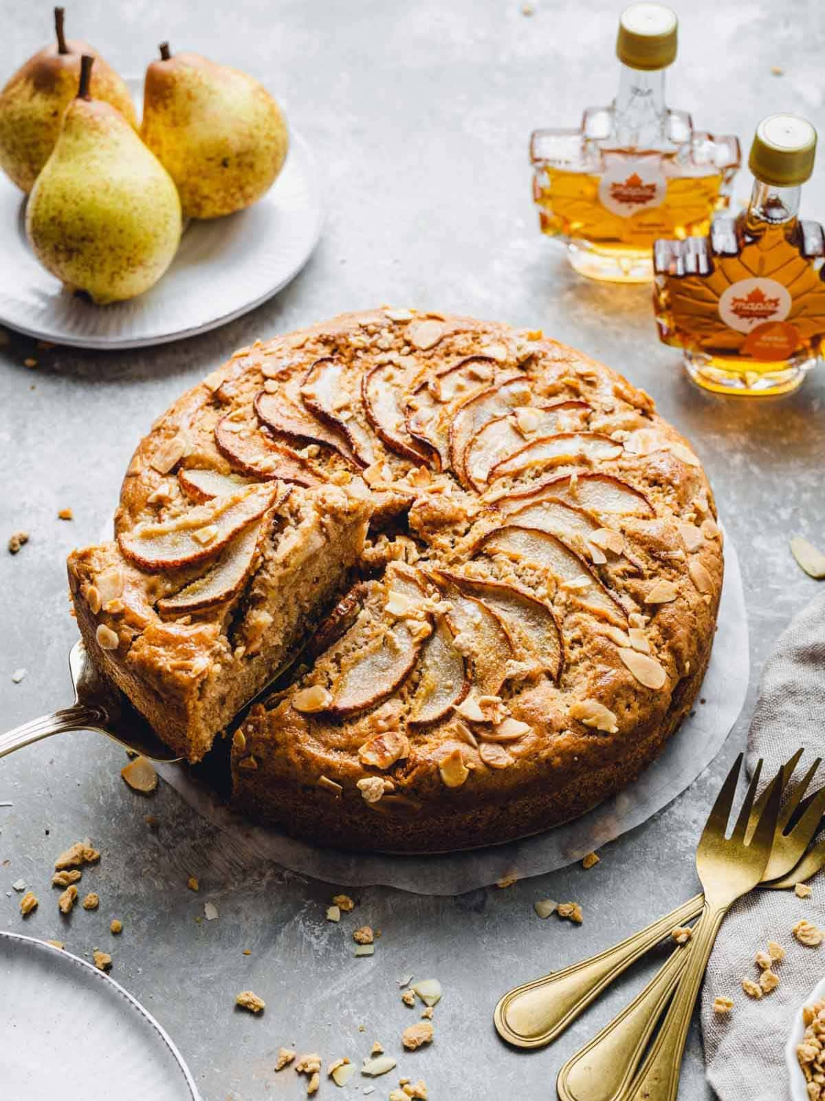 A side view of a pear cake with one slice being taken out.