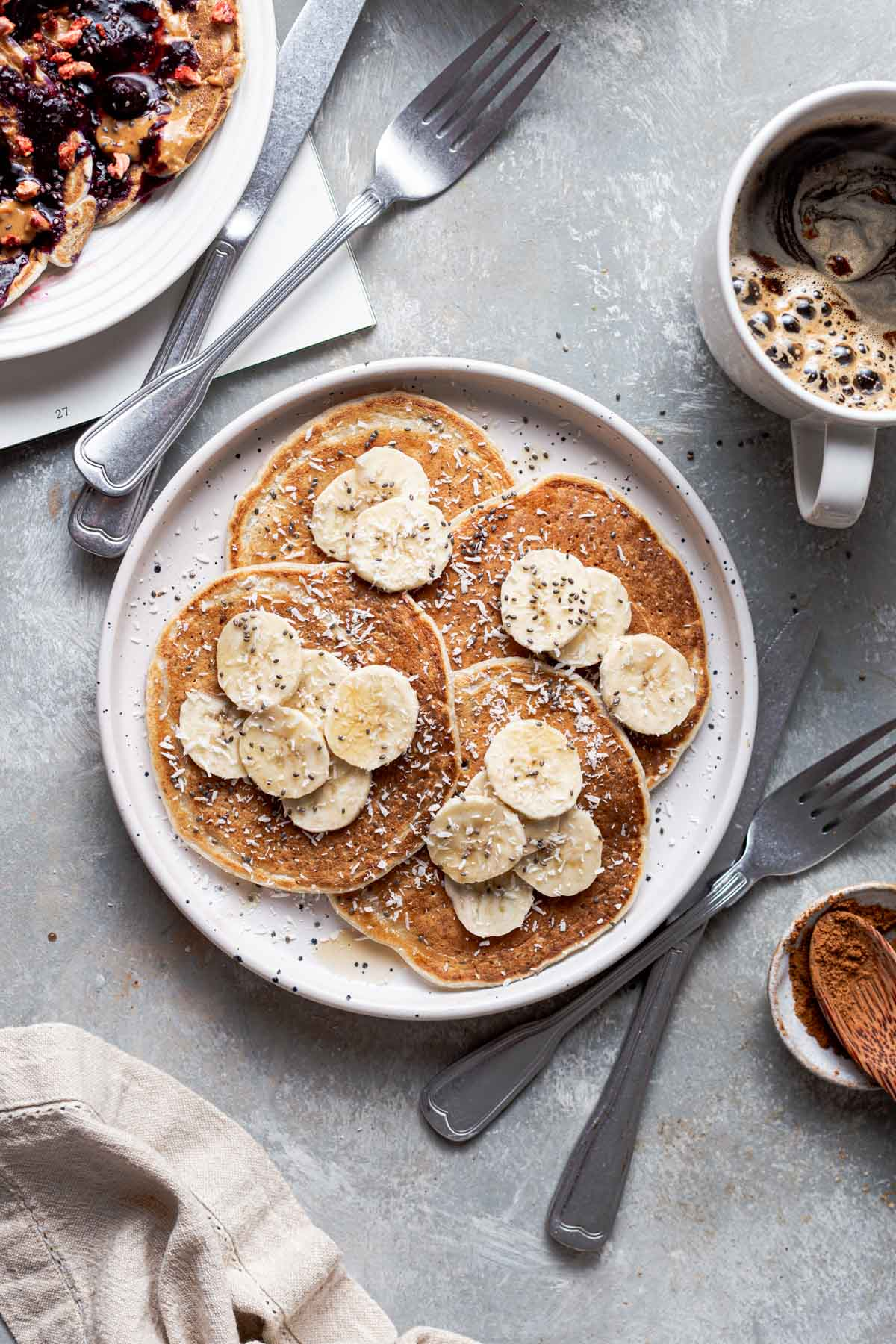 A plate full of vegan pancakes topped off with slices of banana.