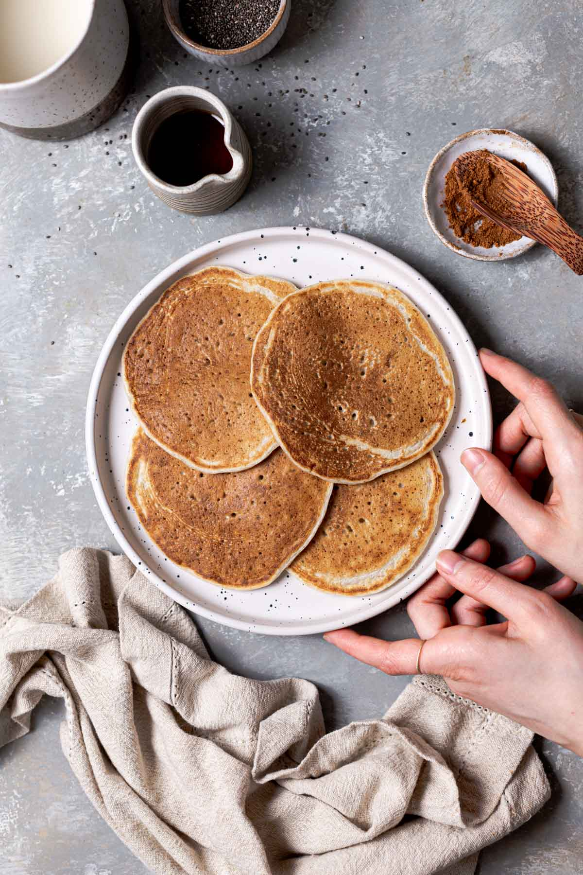 Four plain vegan pancakes on a white plate with two hands holding the sides and a piece of linen next to it.