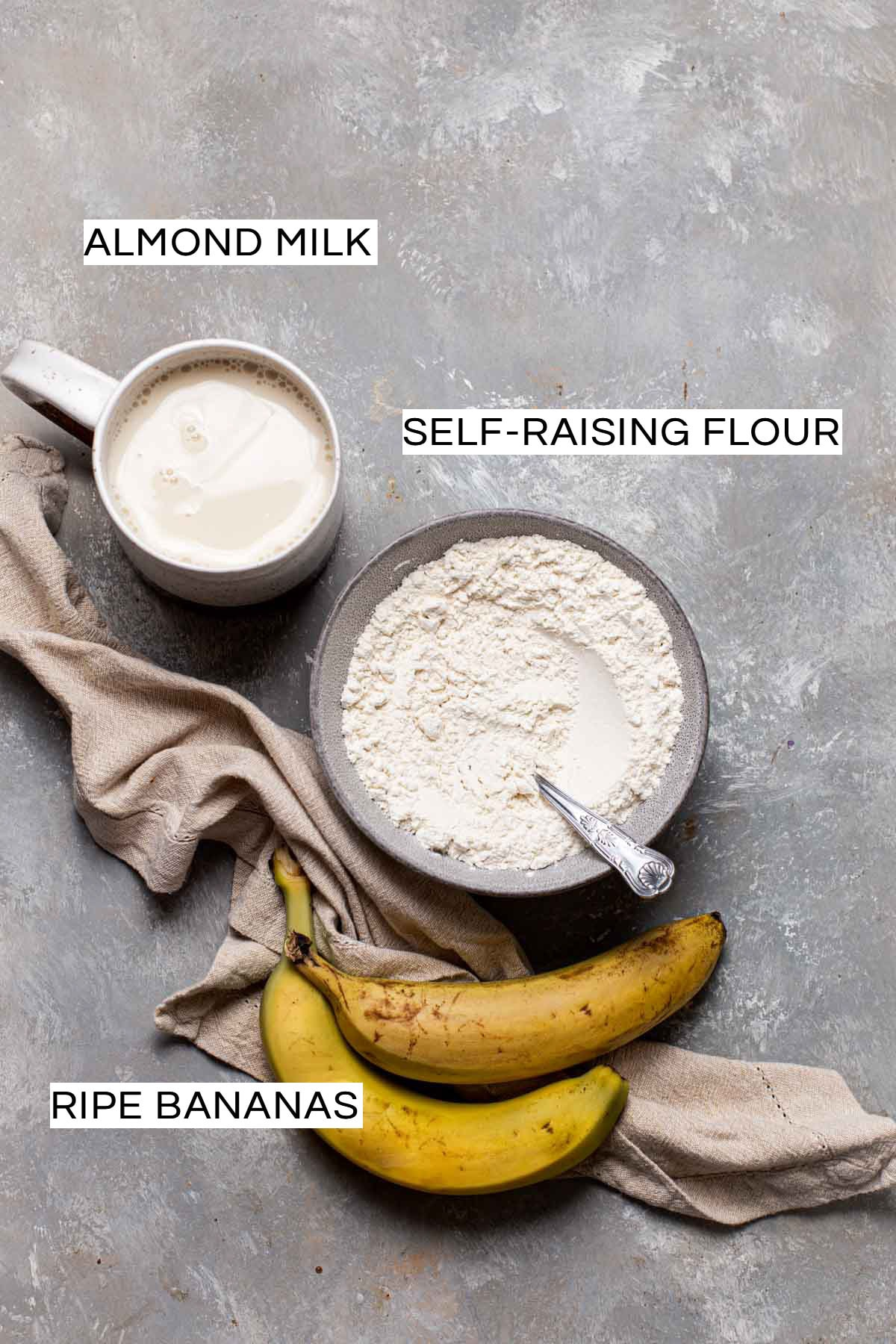 All ingredients needed to make a vegan pancake laid on a flat grey surface.