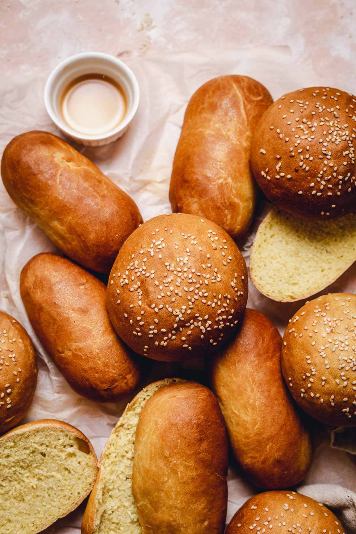 Several bread buns and hotdog buns placed on top and next to each other on crumpled baking paper.