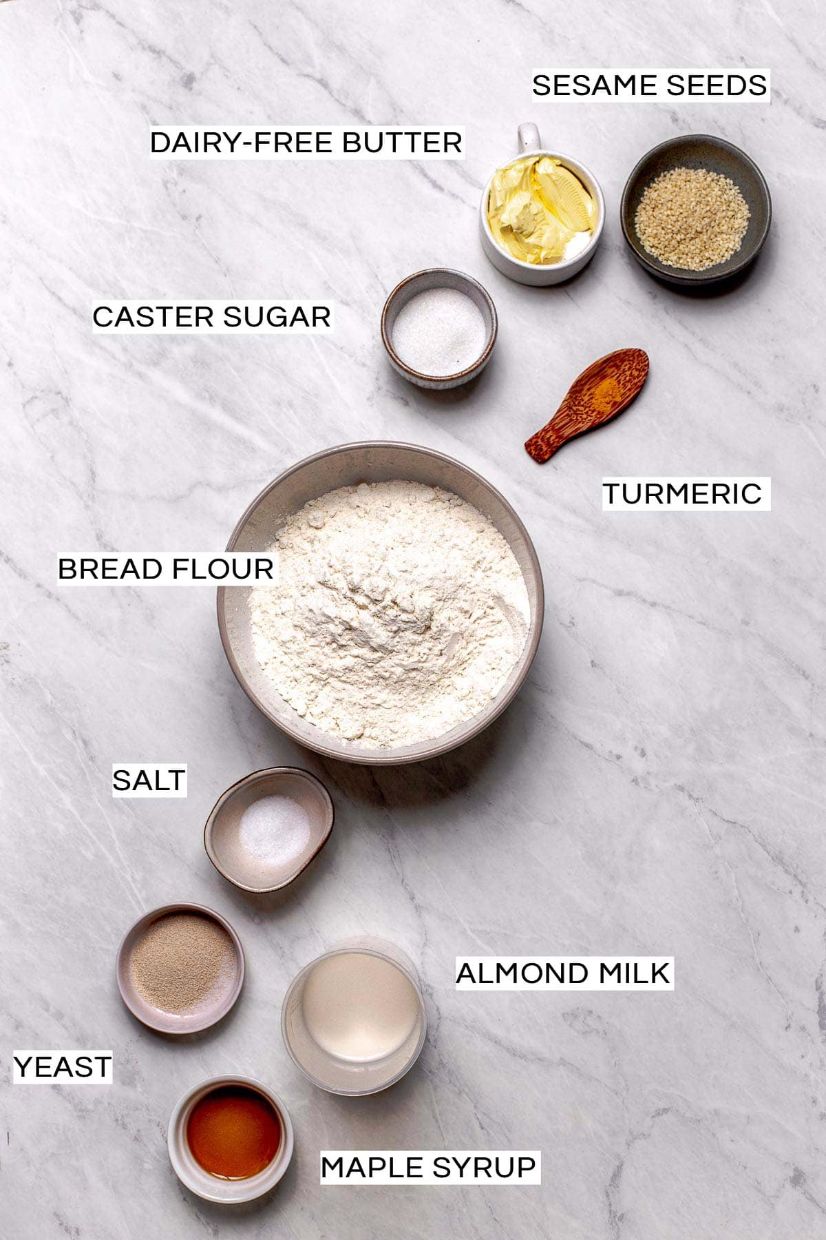 All ingredients needed to bake vegan burger buns laid out on a marble surface.