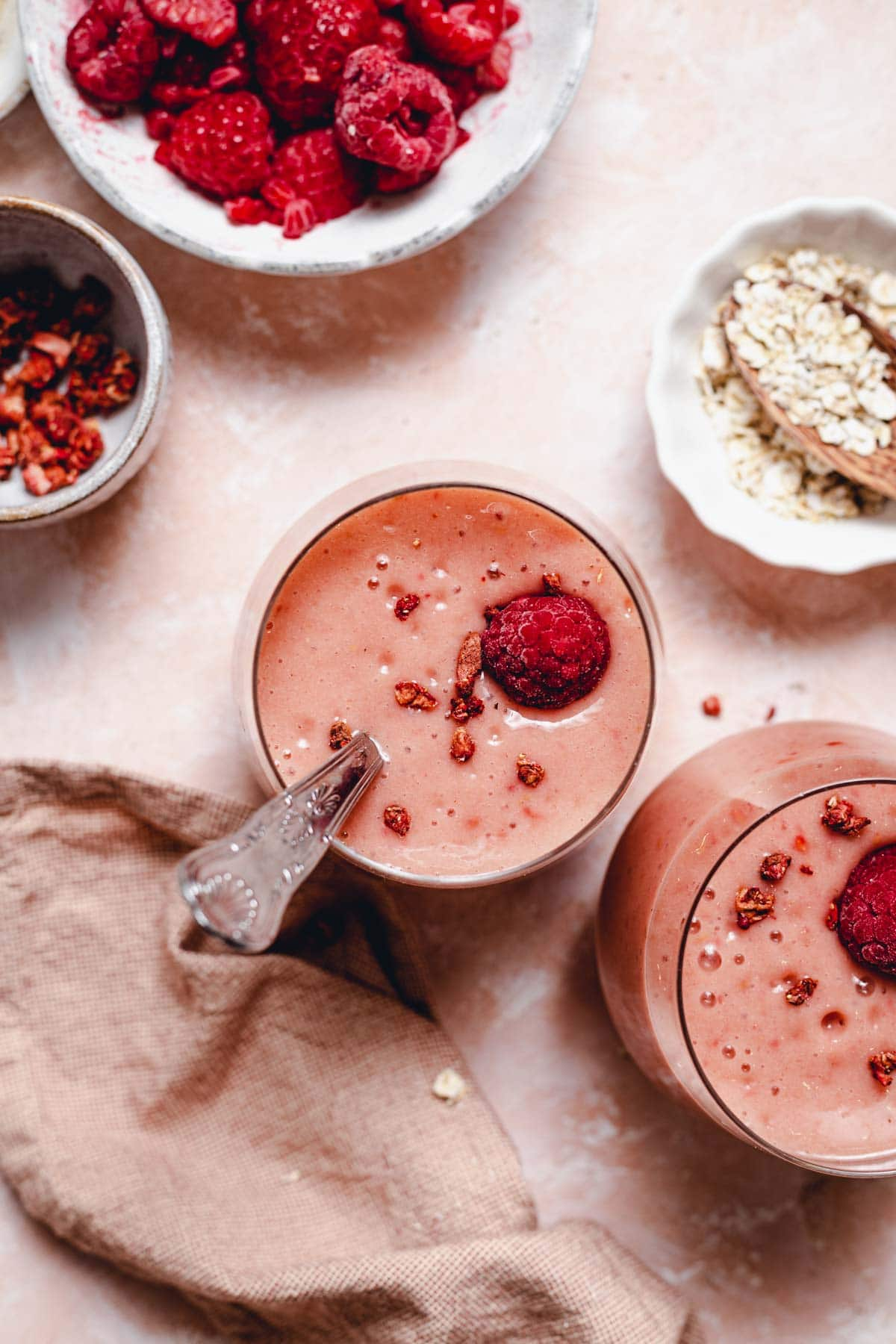 Two glasses of pink coloured smoothie on a flat background with raspberries, oats and a napkin laid next to them.