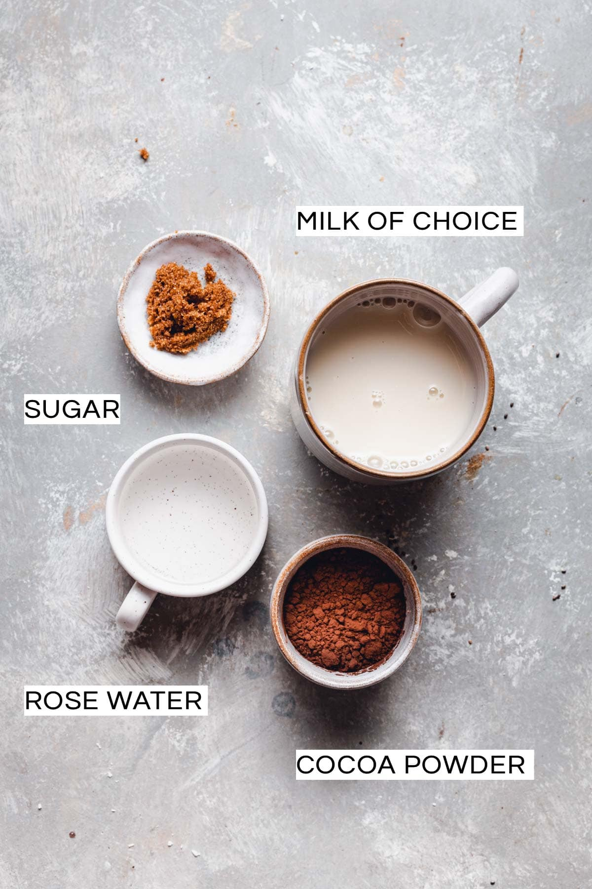 All four ingredients needed to make rose hot chocolate in bowl placed on a flat grey surface.