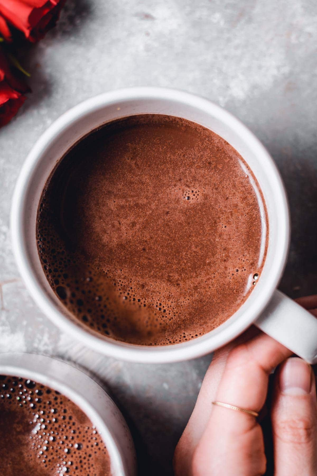 A close-up view of a mug of freshly made hot chocolate with bubbles on top and a hand holding the handle.