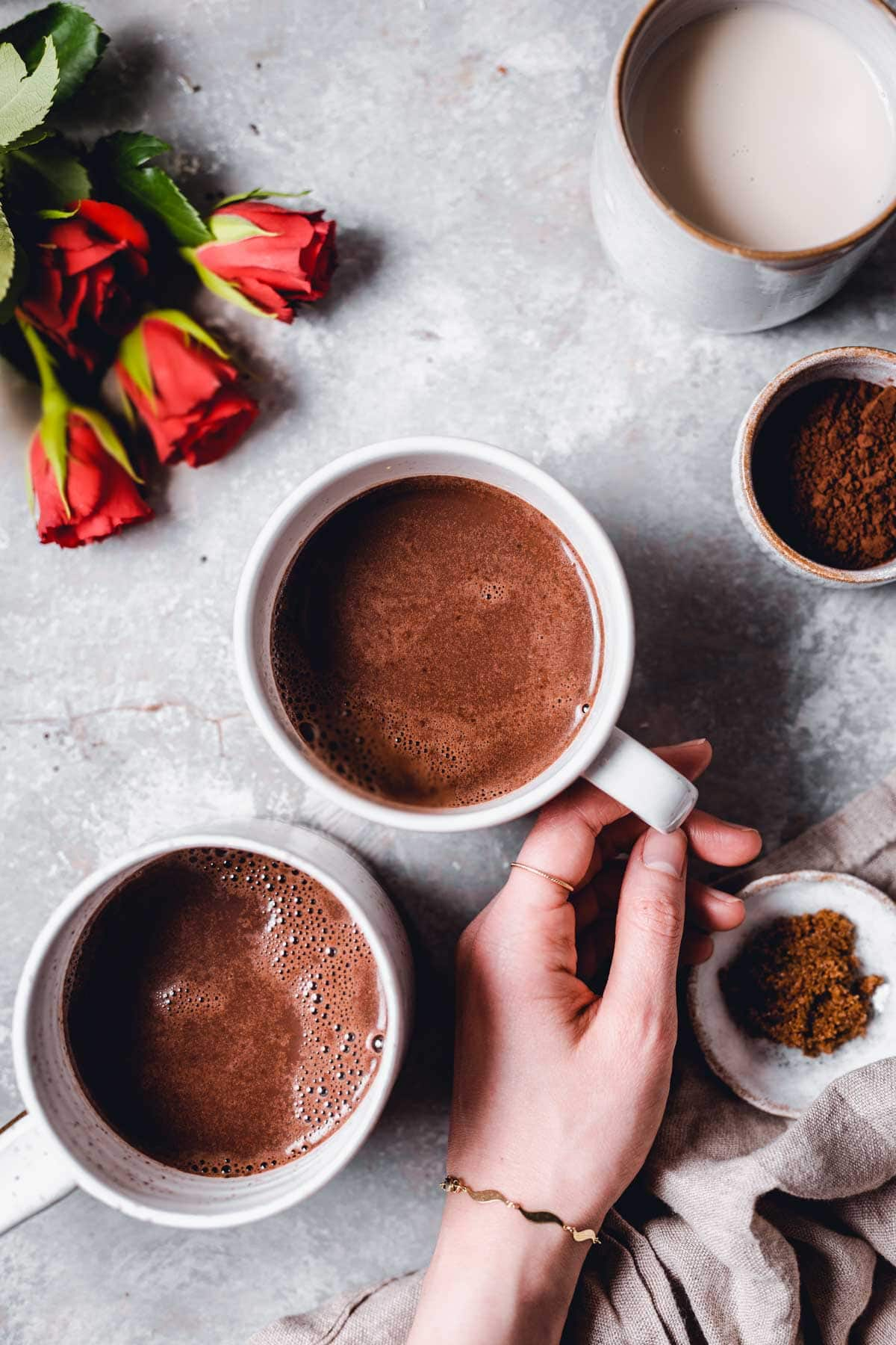 A hand holding one mug of hot chocolate with various props like roses, cocoa, milk and napkins scattered around it.