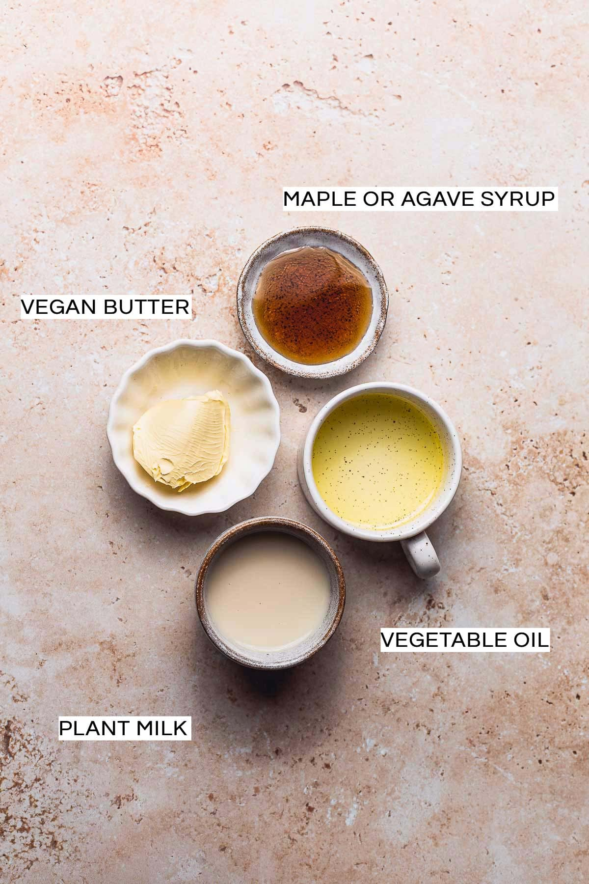 Four staple vegan egg wash ingredients in bowls on a rusty background.