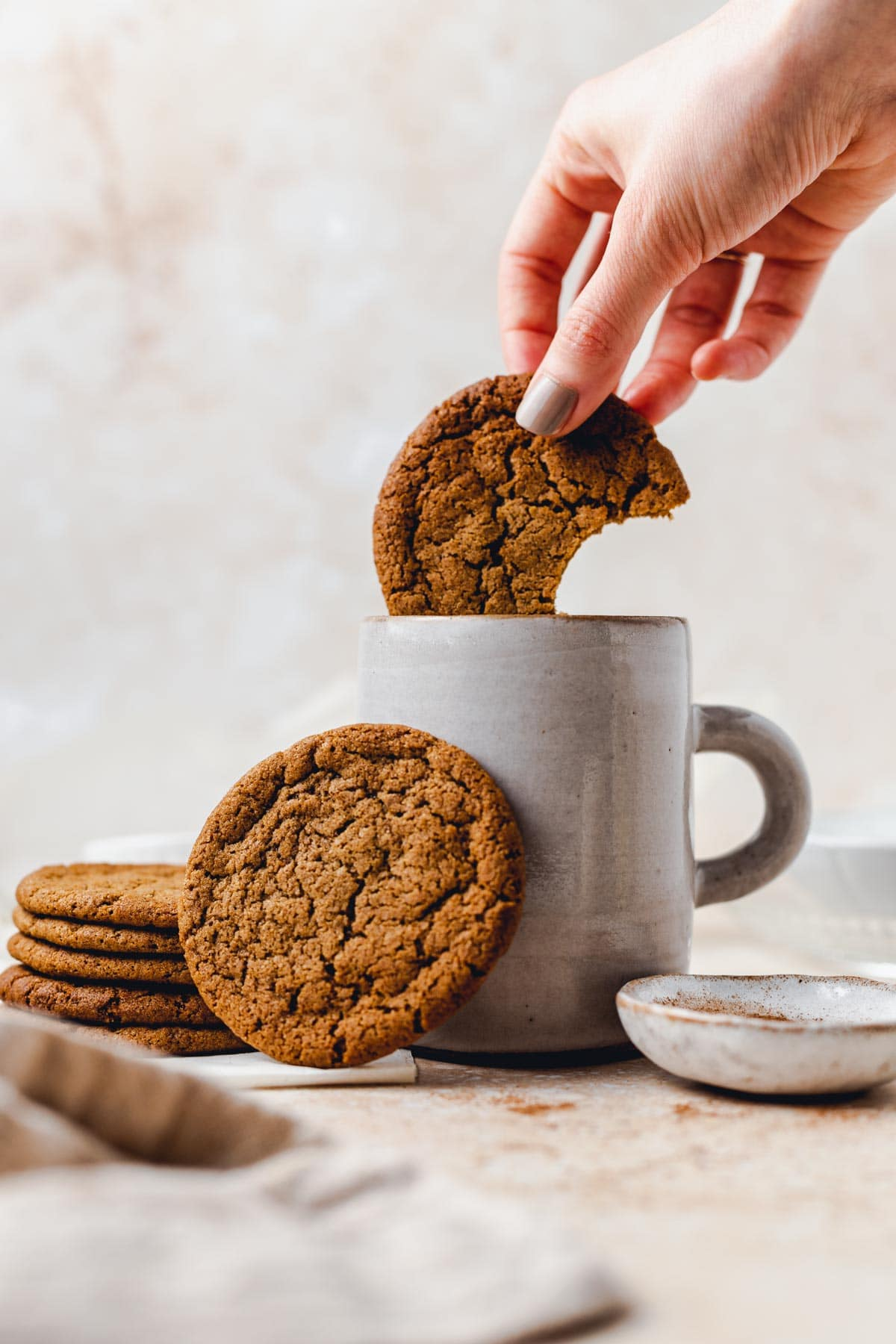 A hand dipping a ginger cookie in a mug of milk.