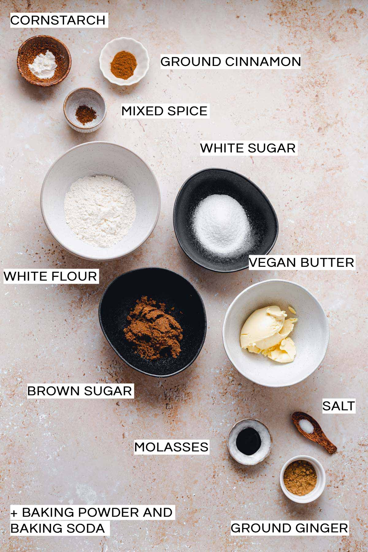 Various ingredients needed to make vegan ginger cookies placed on a flat surface.
