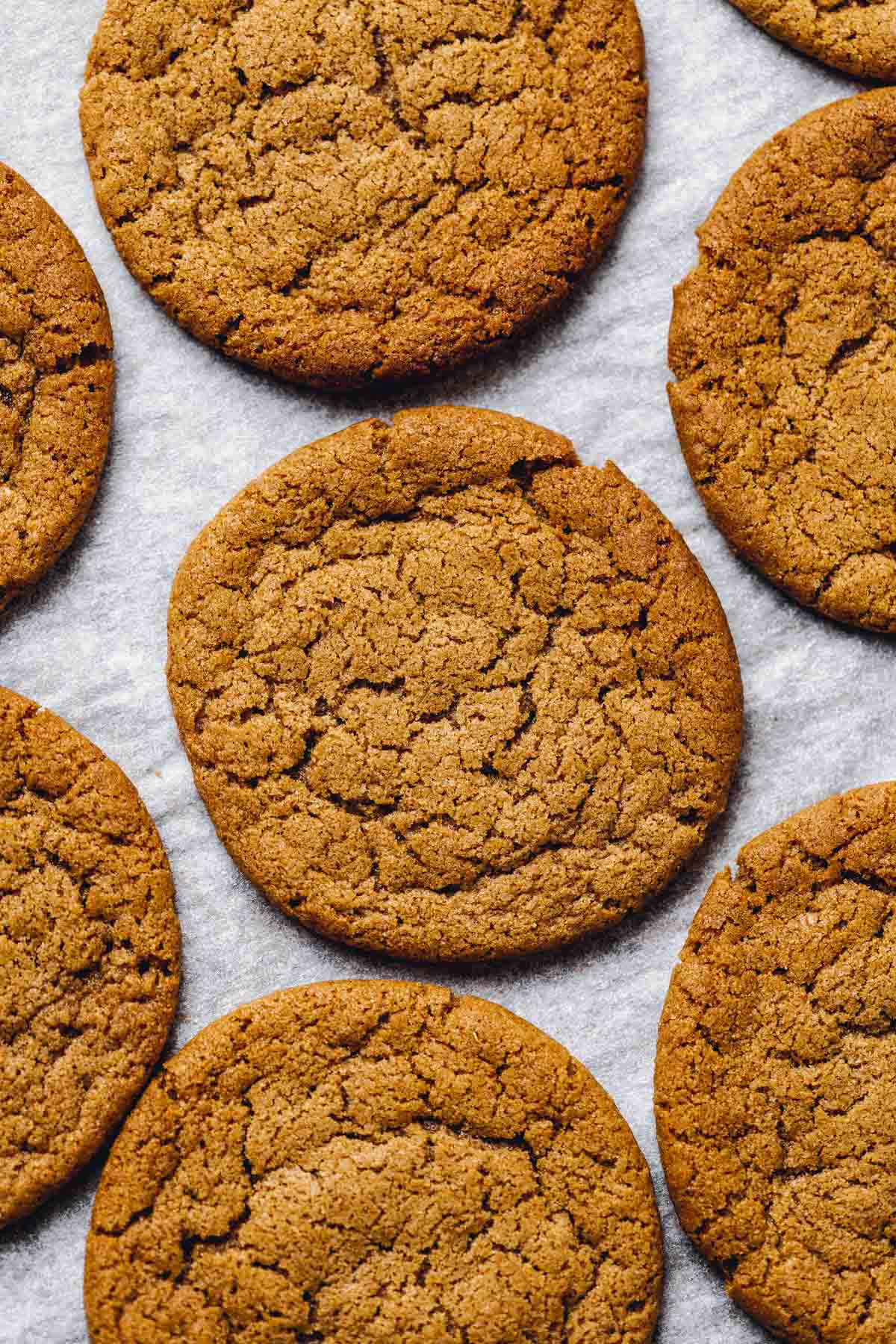 A close-up image of vegan ginger cookies on a sheet of white baking paper.