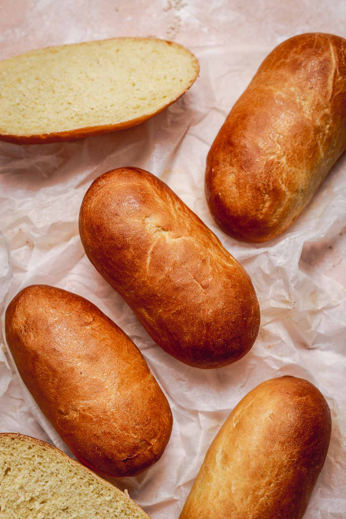 Freshly baked hot dog buns with a glossy glaze placed on a sheet of parchment paper.