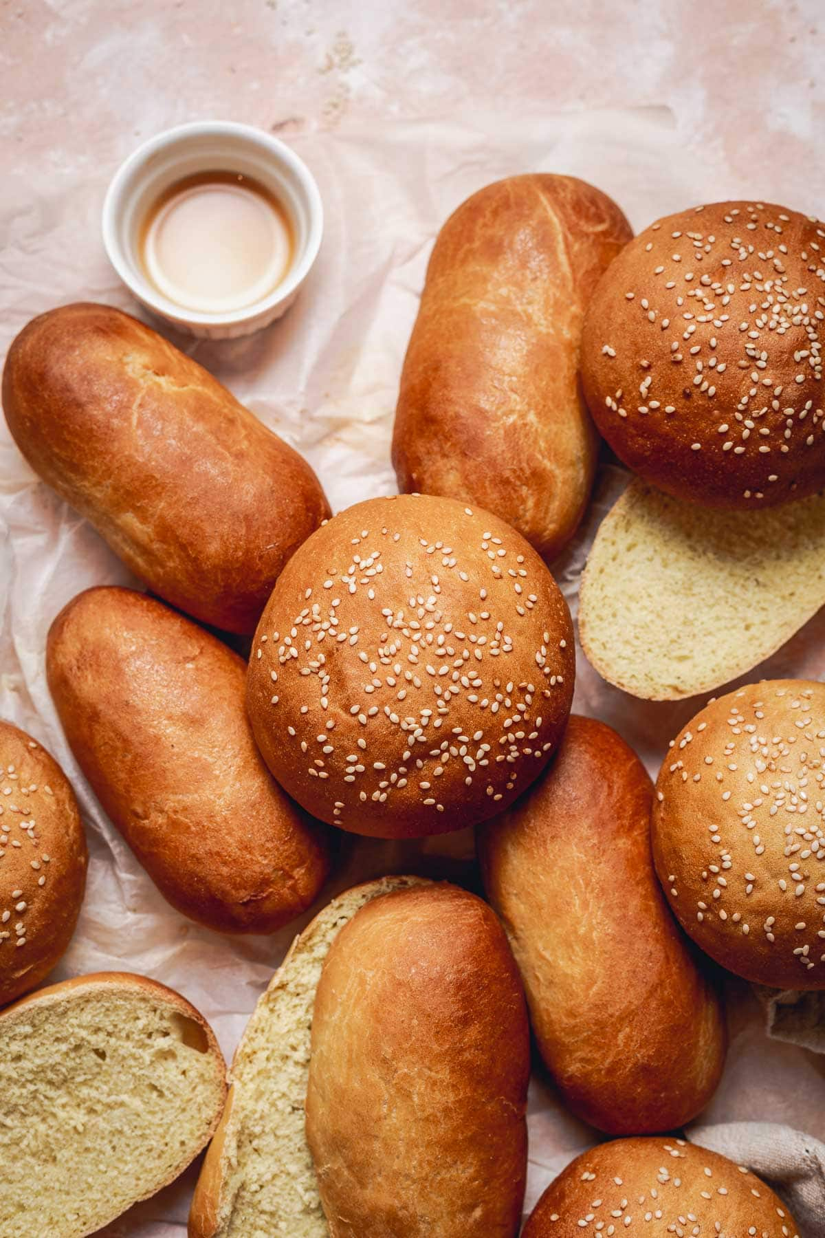 A group of baked bread including hot dog buns and sesame topped burger buns placed on crumpled baking paper.