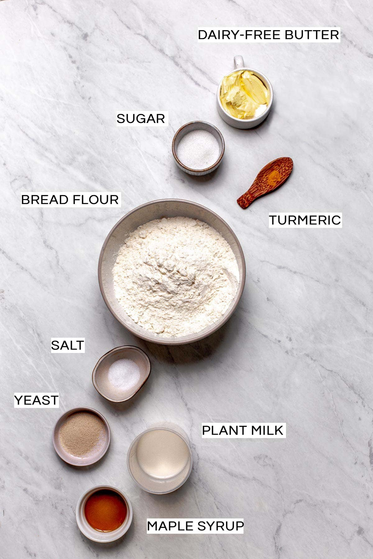 All ingredients needed to bake vegan hot dog buns laid out on a marble surface.