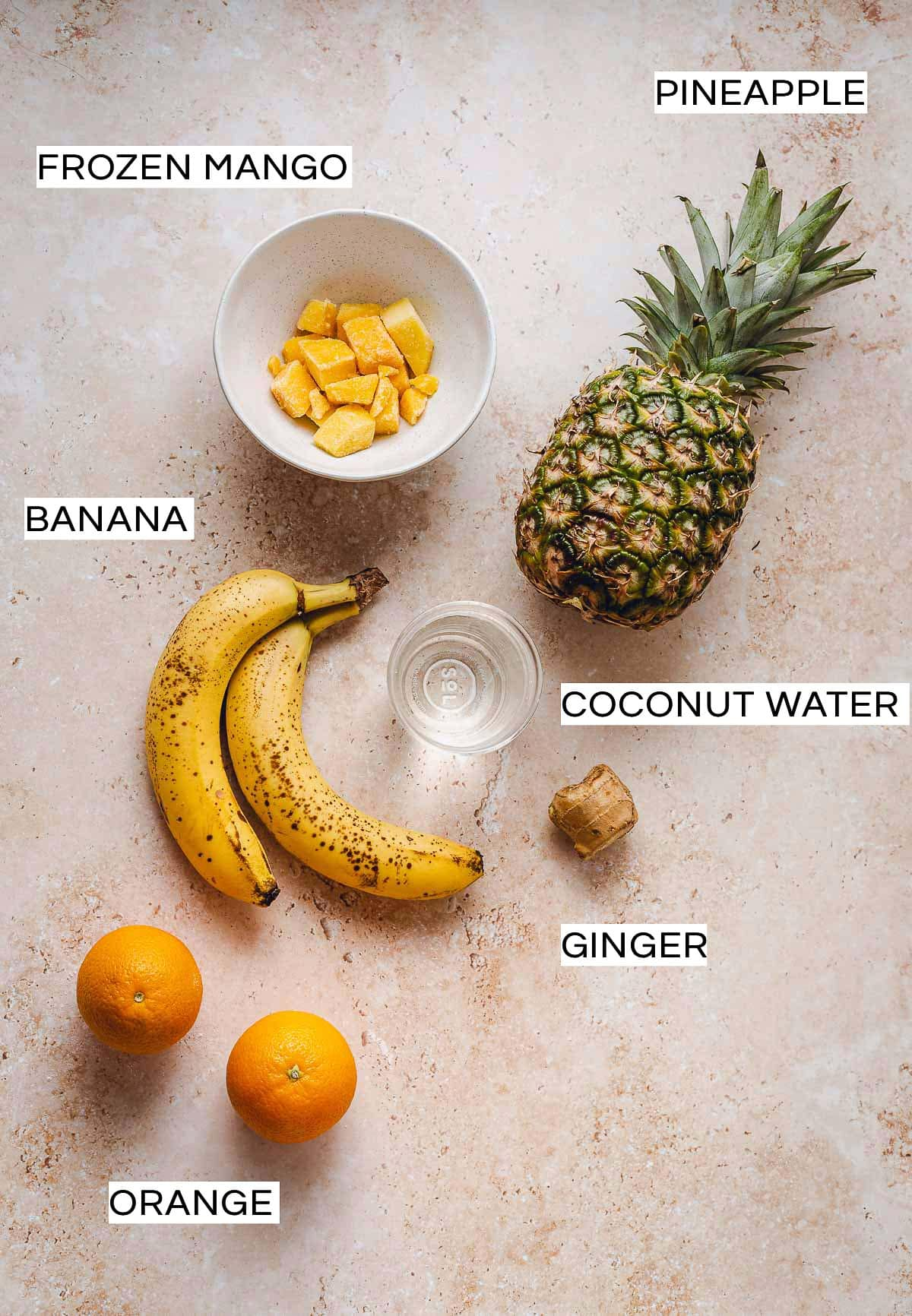 All ingredients needed to make a vegan tropical smoothie laid out on a flat surface.