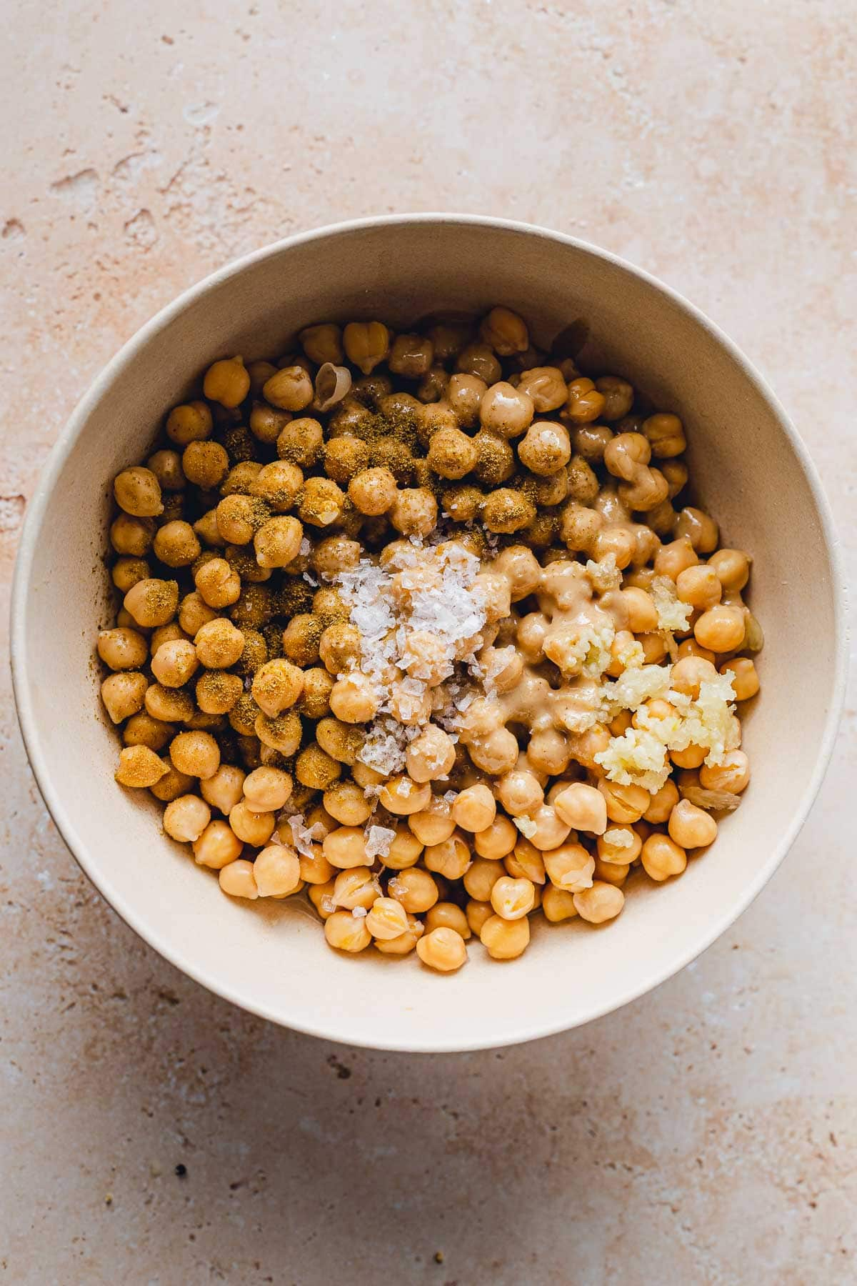 A large bowl with chickpeas, salt, minced garlic and other hummus ingredients prior to blending