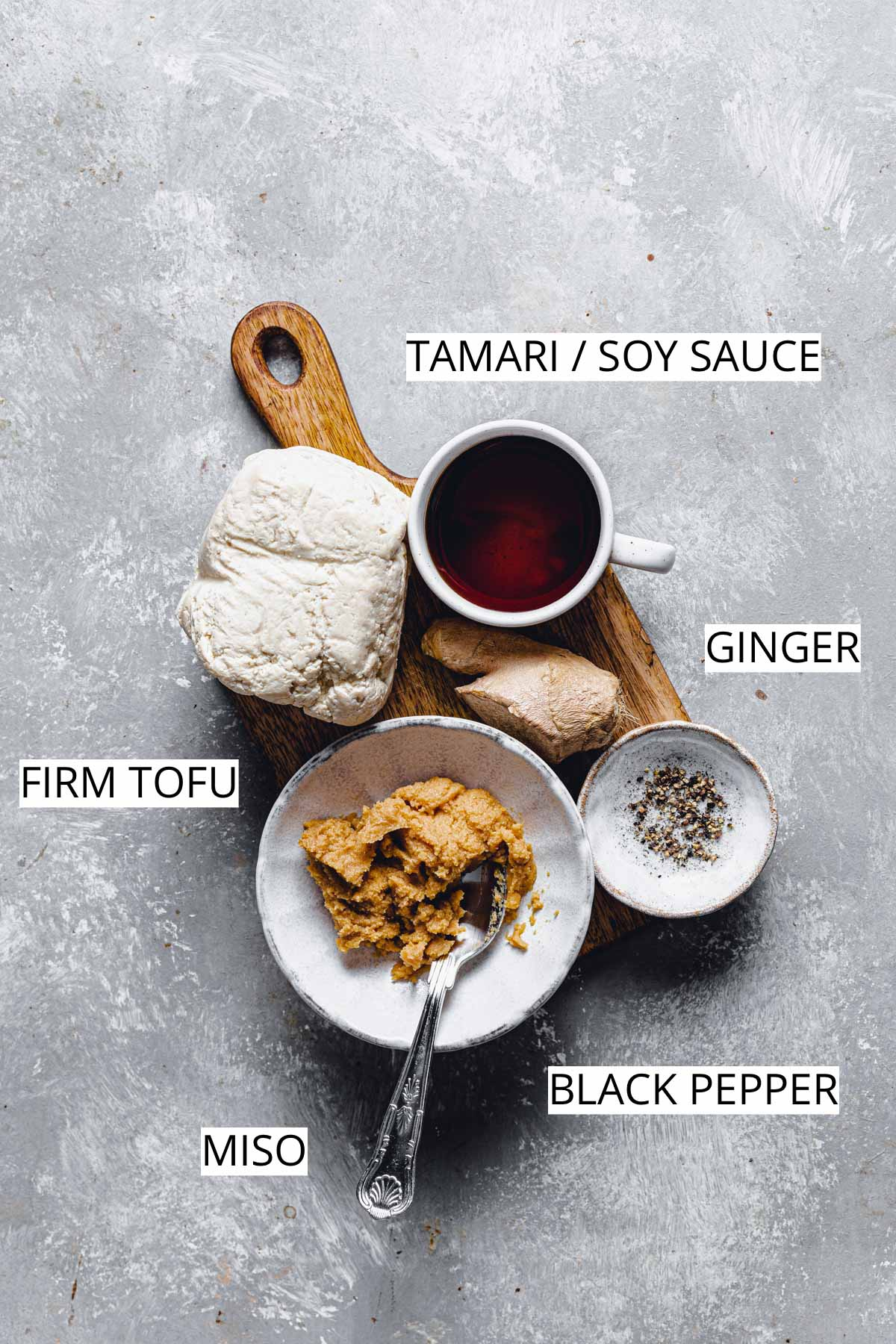 All 4 ingredients needed to make miso marinated tofu placed on a small wooden chopping board.