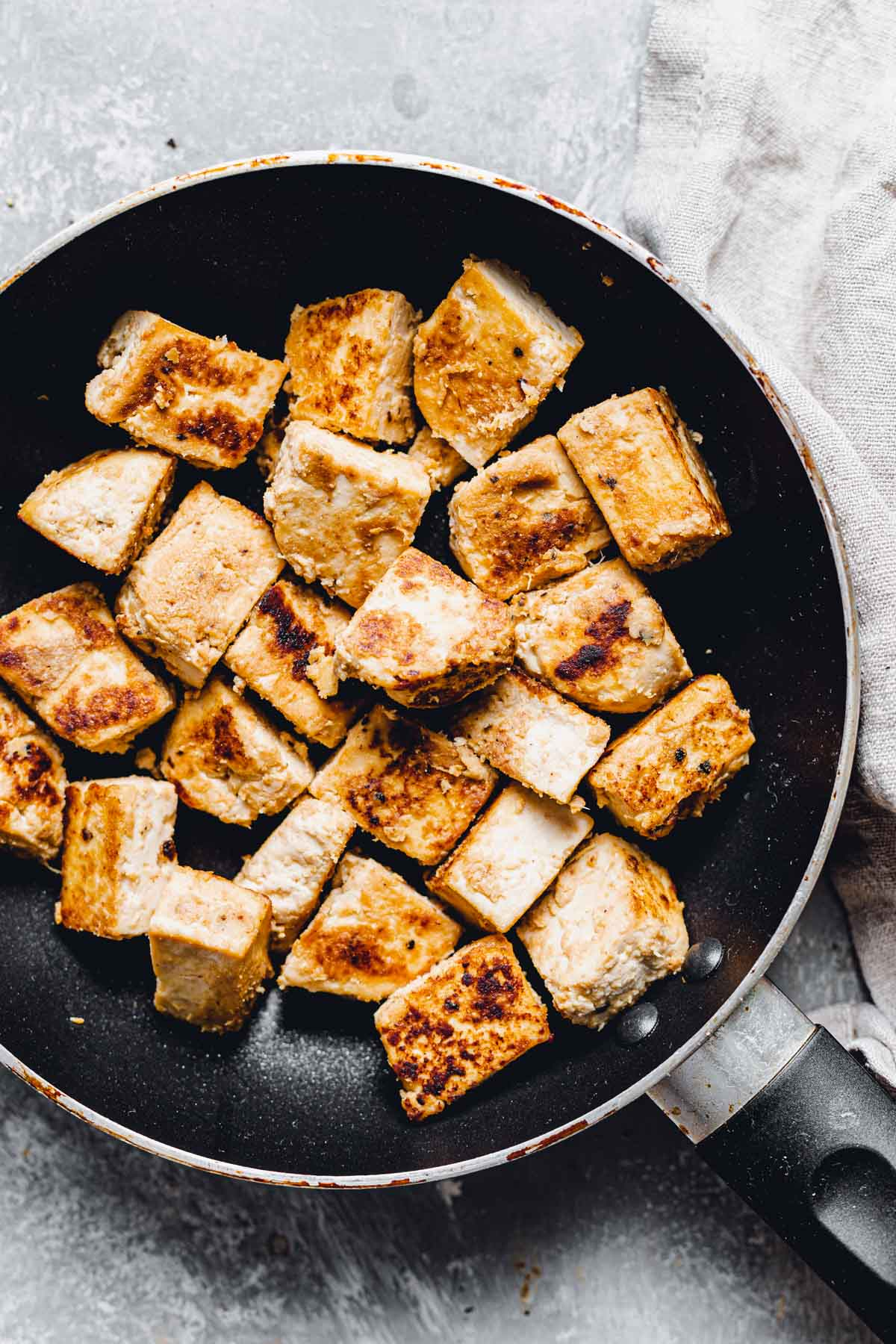 An overhead view of a large black frying pan with tofu cubes in it.