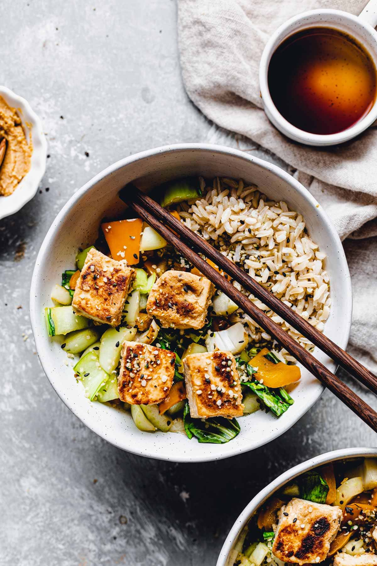 A bowl of rice, tofu and veggies with two wooden chopsticks placed in the middle.