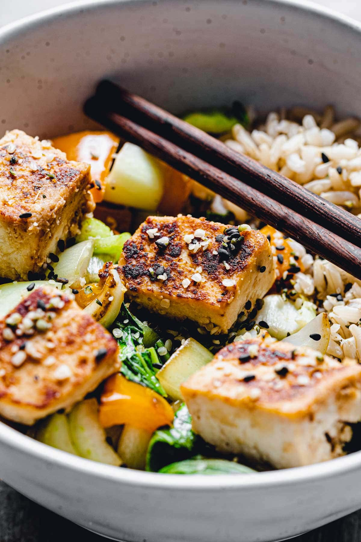 A close-up view of a bowl of stir-fry veggies with focus on a single cube of marinated tofu.