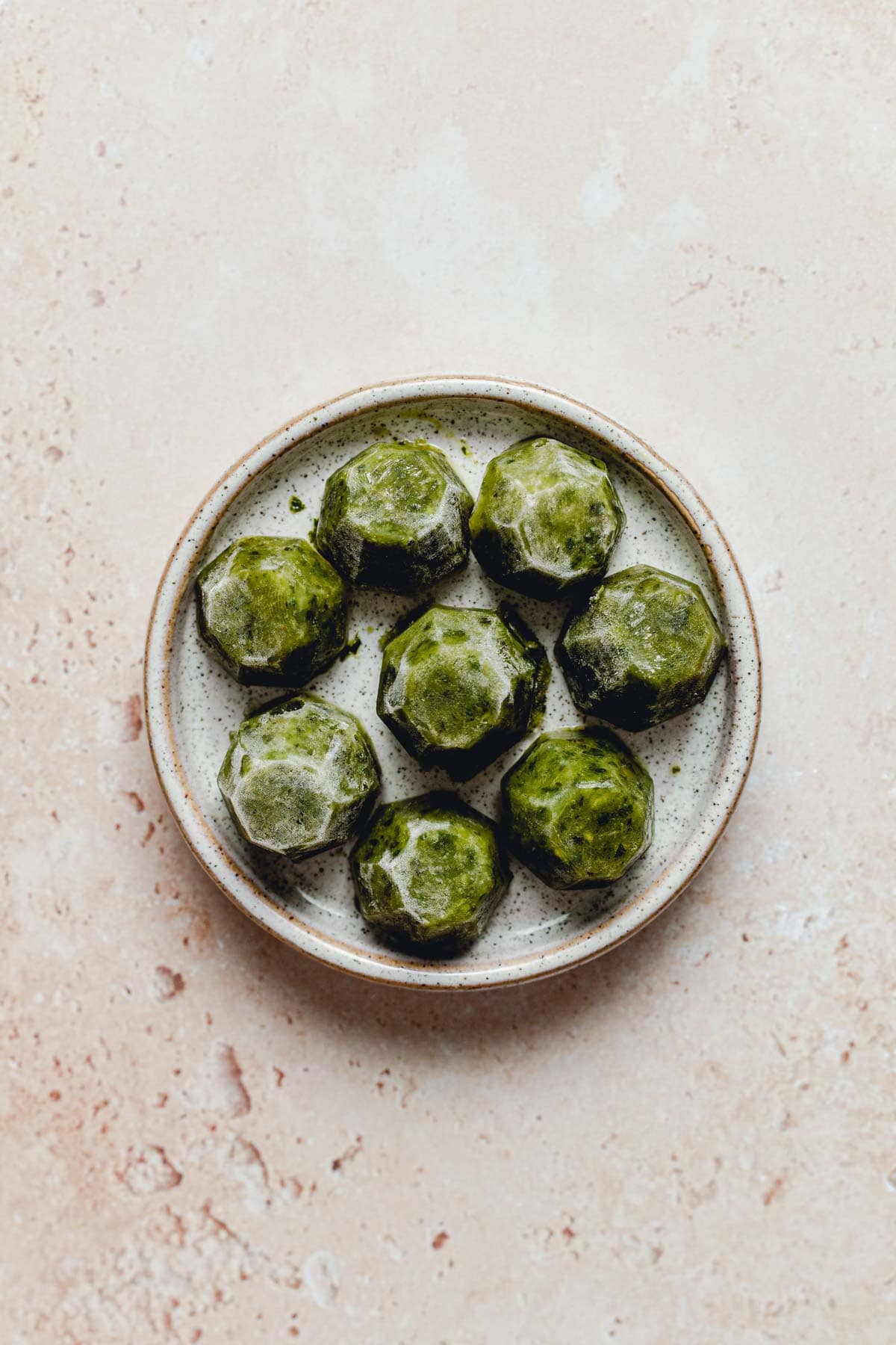 Frozen green chutney cubes placed on a small round plate.