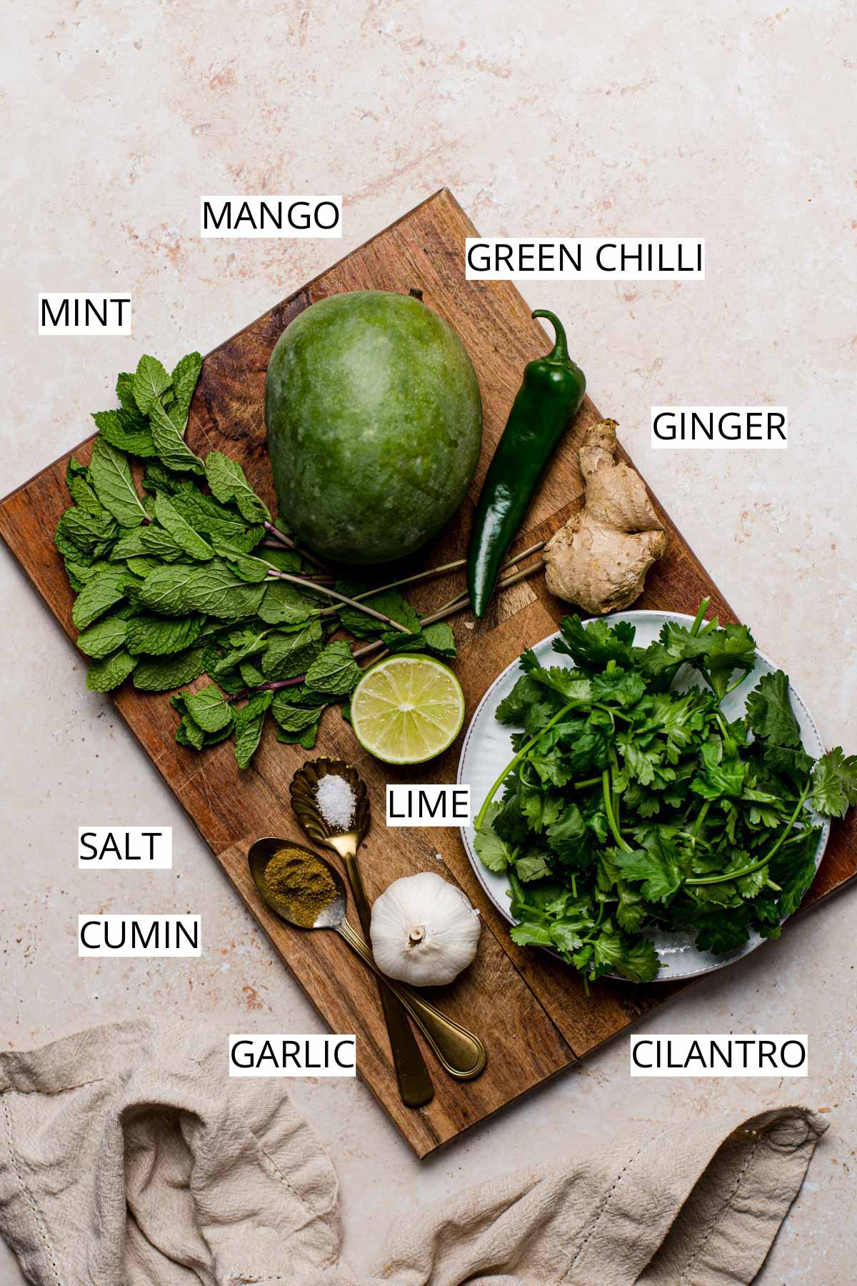 Various ingredients needed to make green mango chutney on a wooden board.