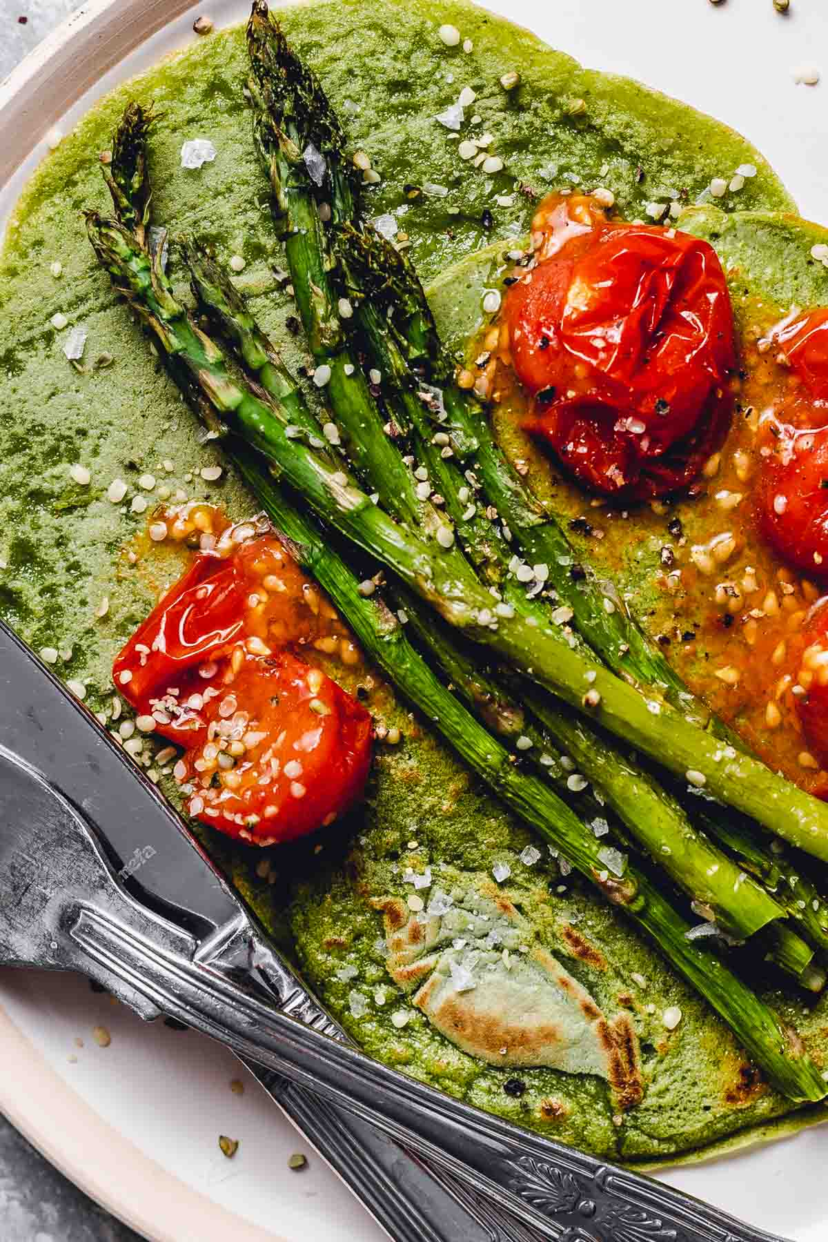 A close-up view of a crepe topped off with tomatoes and asparagus.
