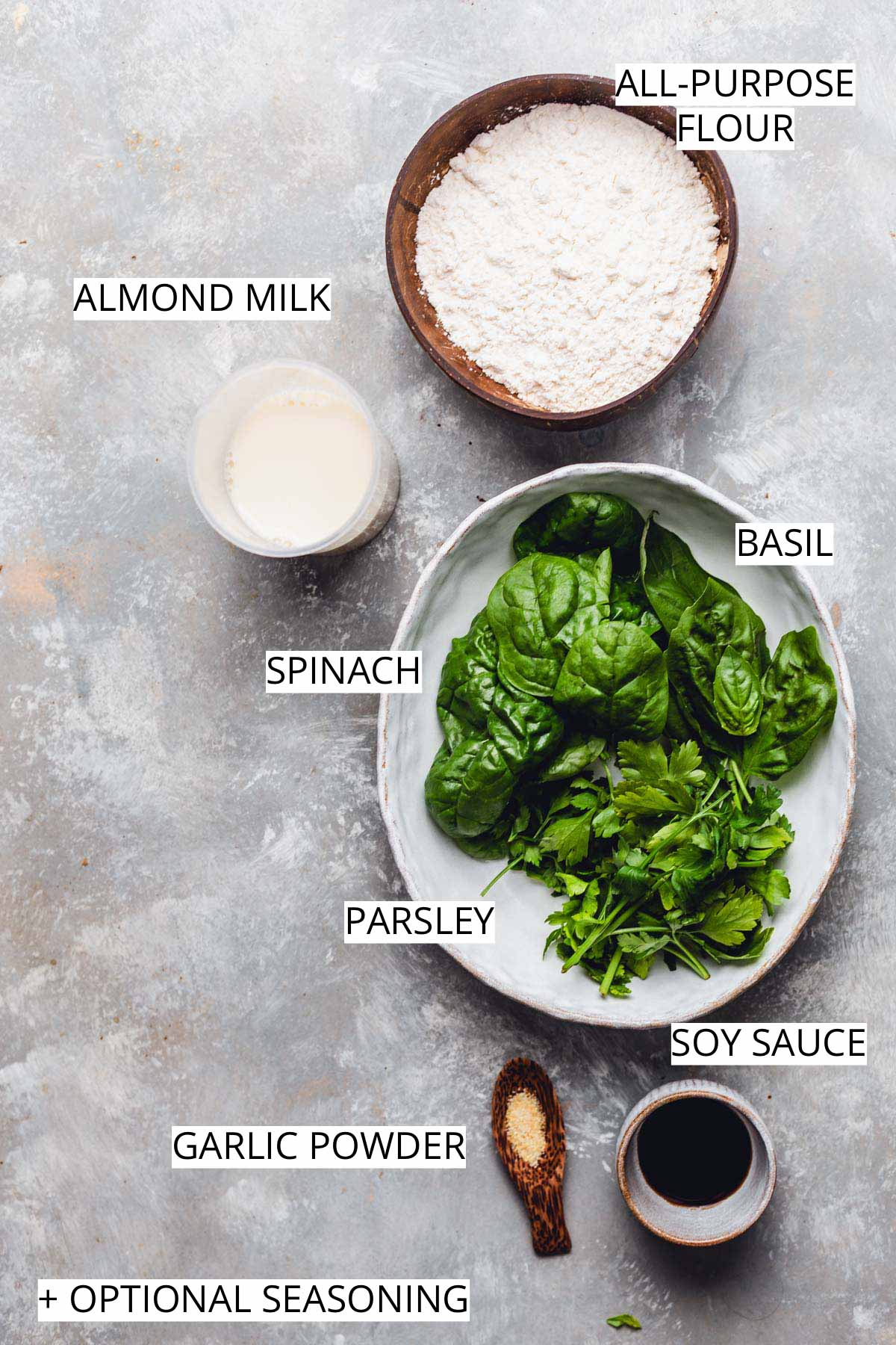 All the ingredients needed to make spinach crepes on a flat grey surface.
