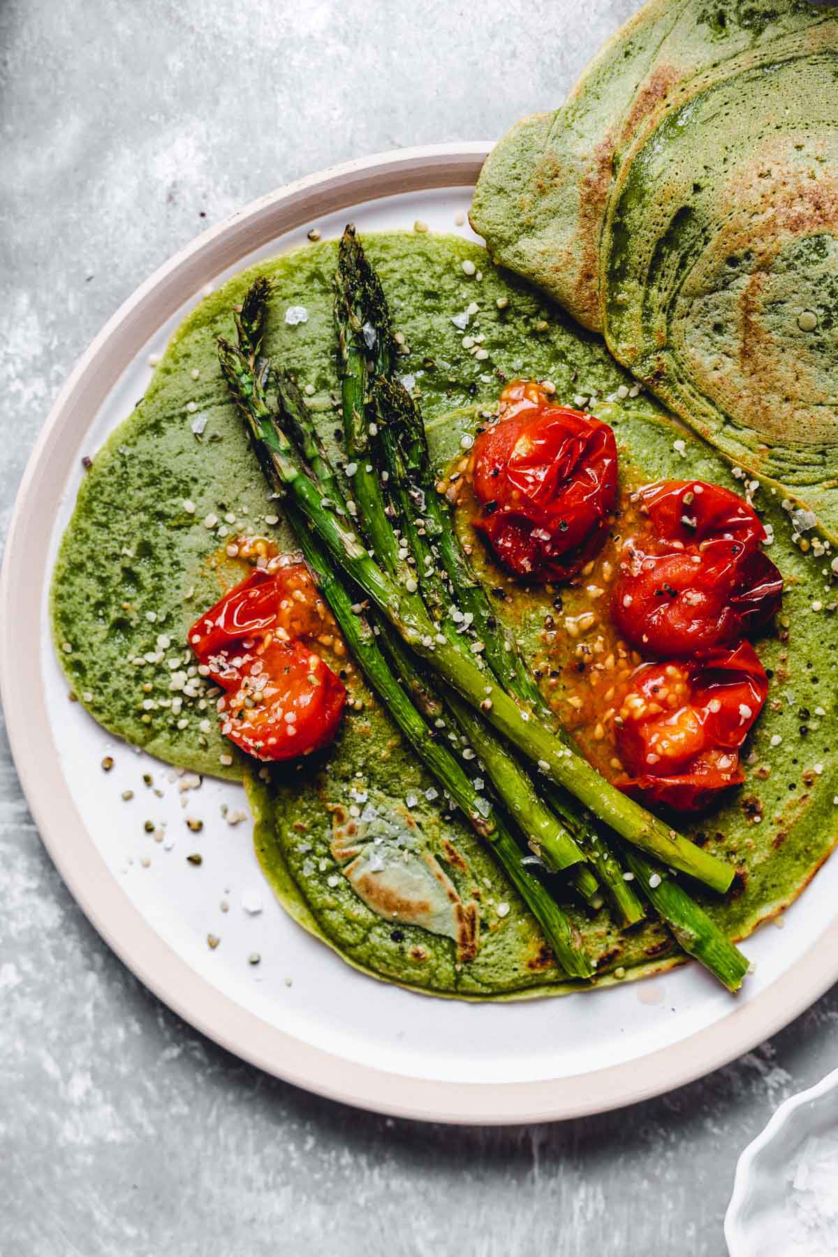 A close-up overhead view of the spinach crepes topped off with tomatoes and asparagus.